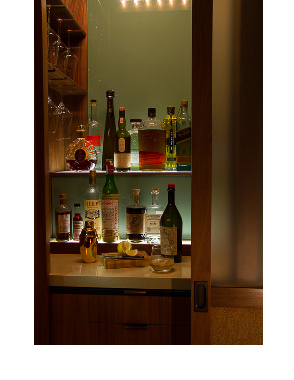 A green glass backdrop was used in this small closet, off the dining area, converted into a bar.