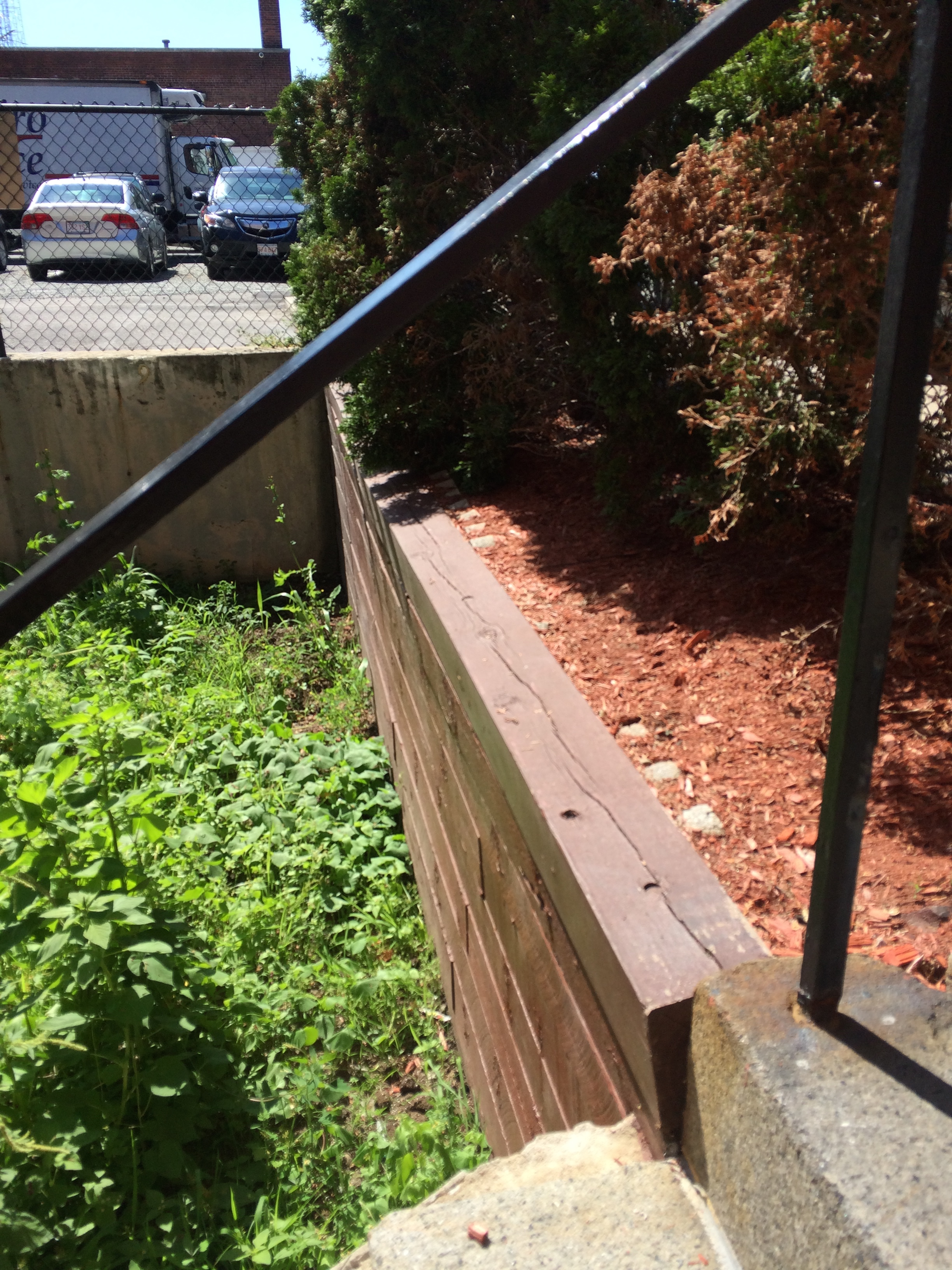 BEFORE - damaged wood retaining wall