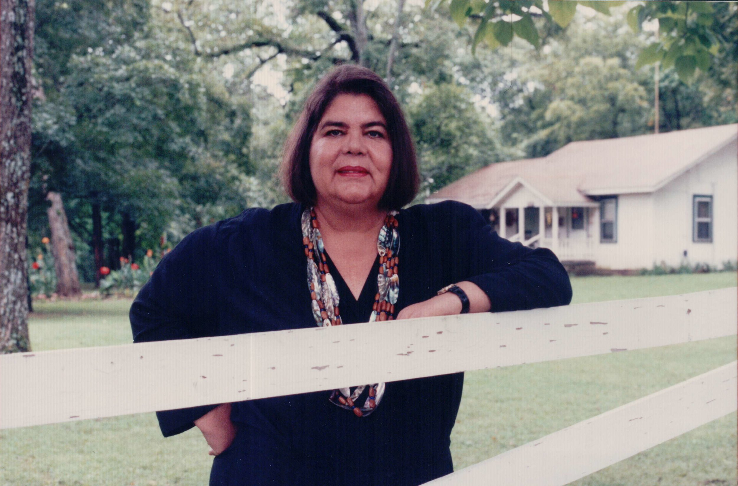 Wilma Mankiller poses by fence