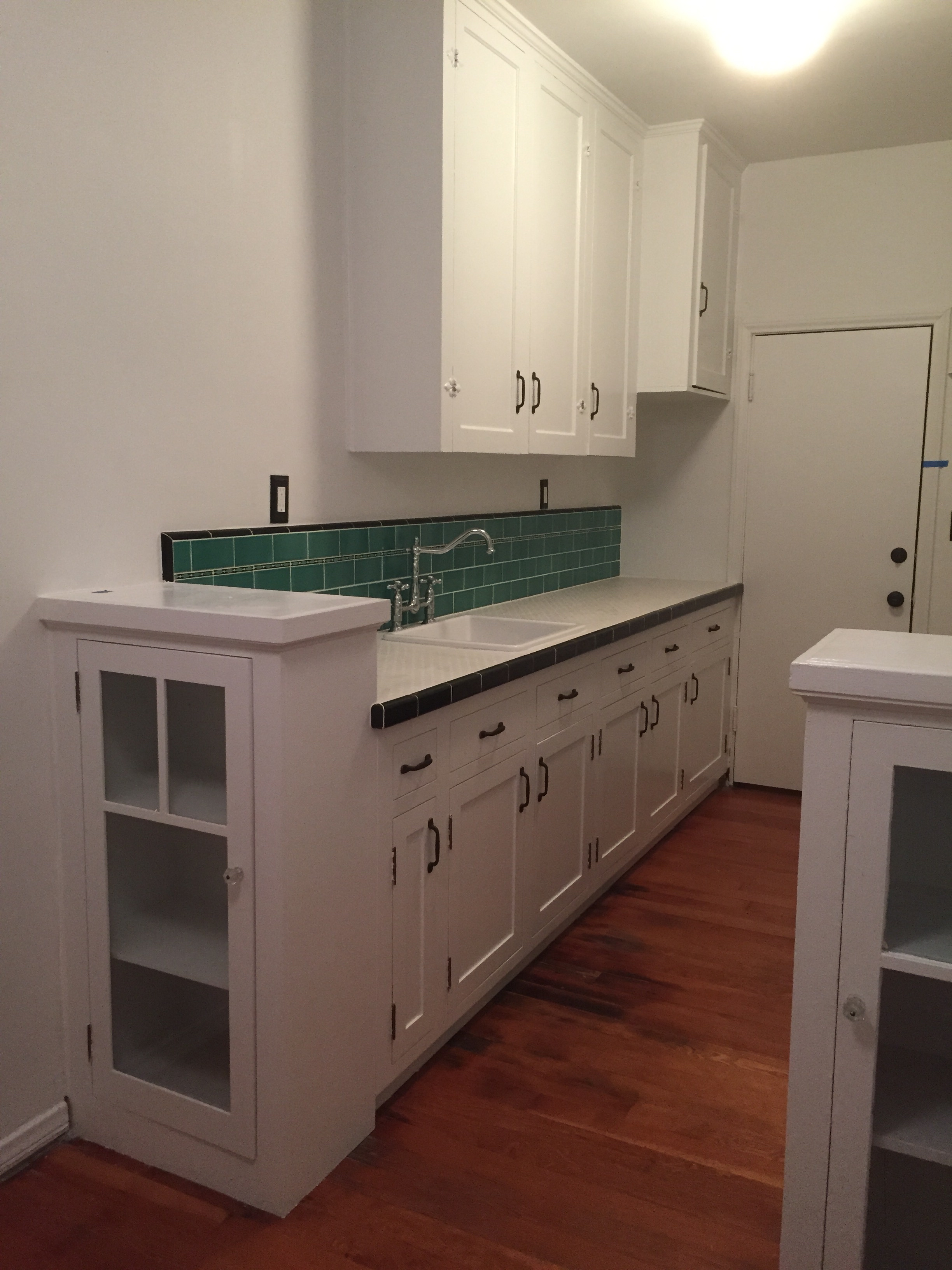 1932 kitchen re-created with reproduction tile, salvaged cabinets, floors and hardware.