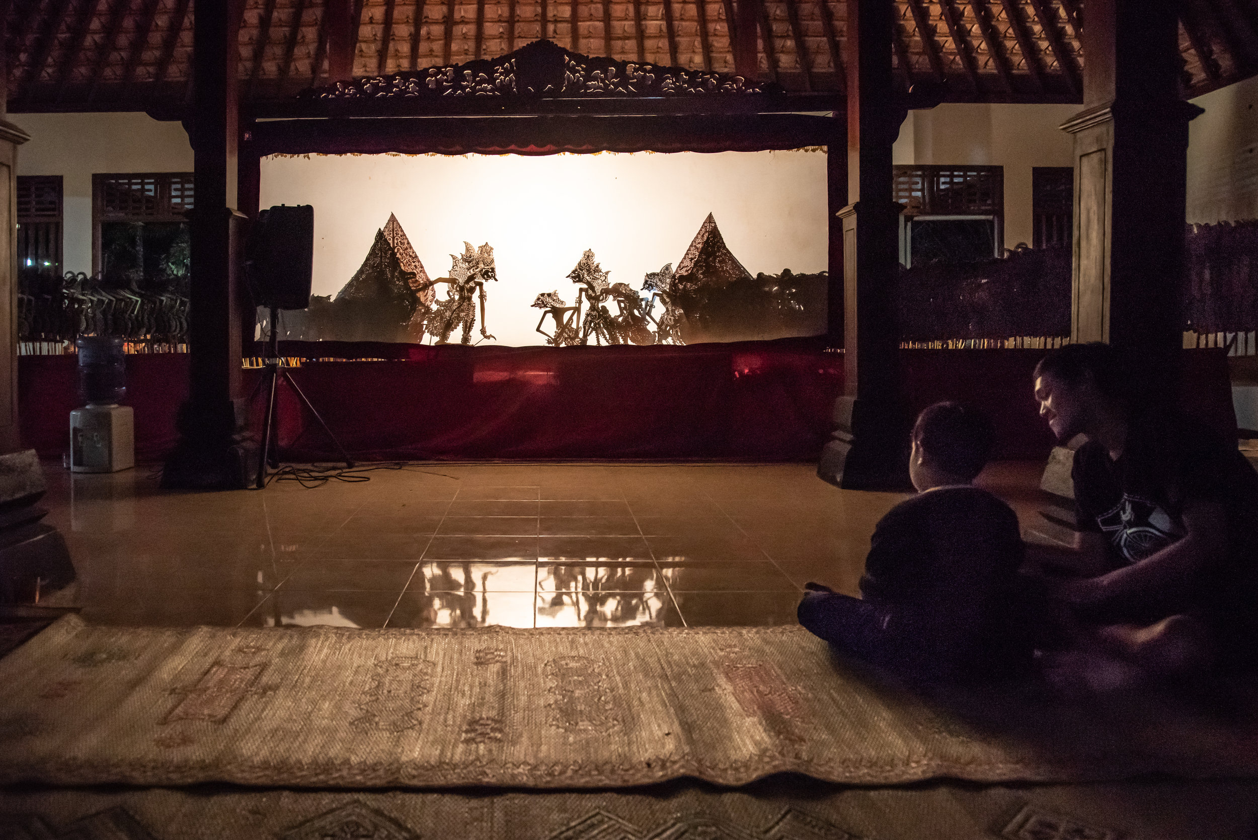 Father and child enjoy the local Wayang Kulit performance