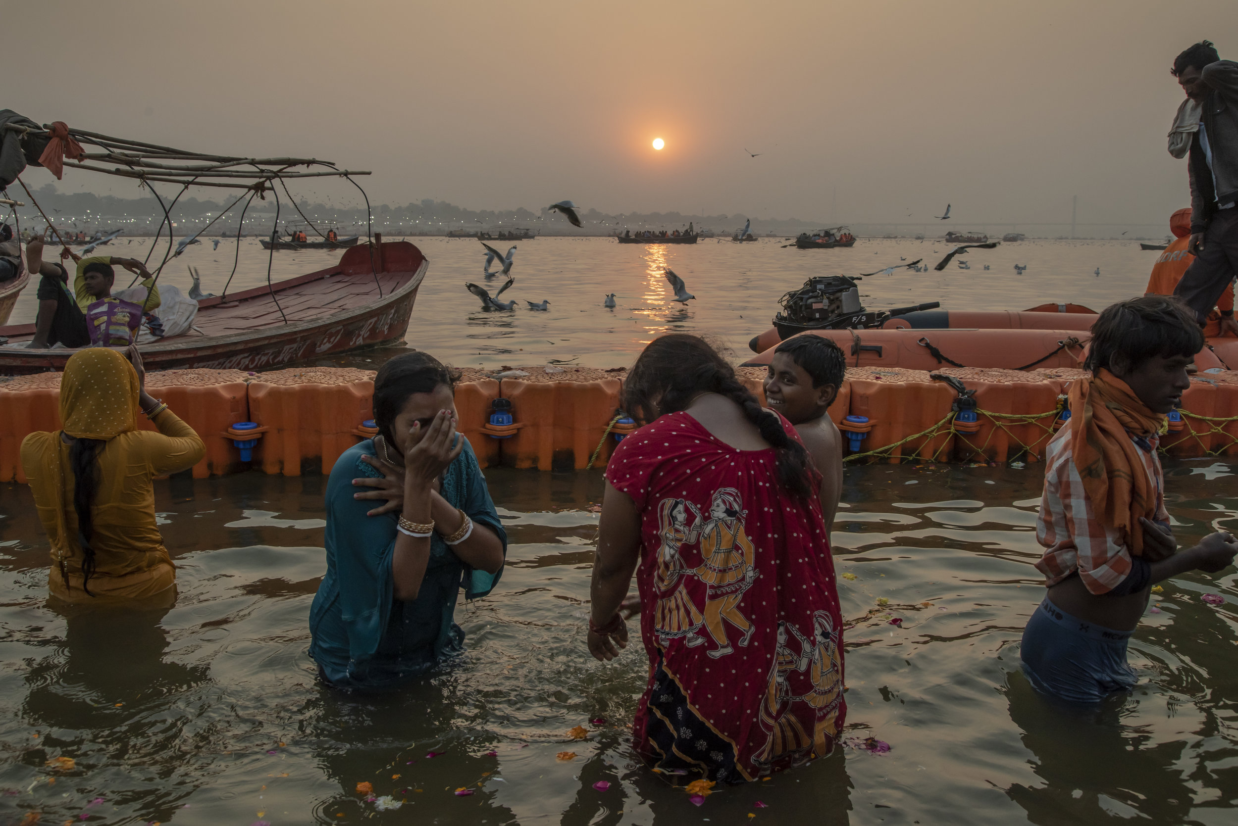 Three young women bathe in the Ganges at sunset.