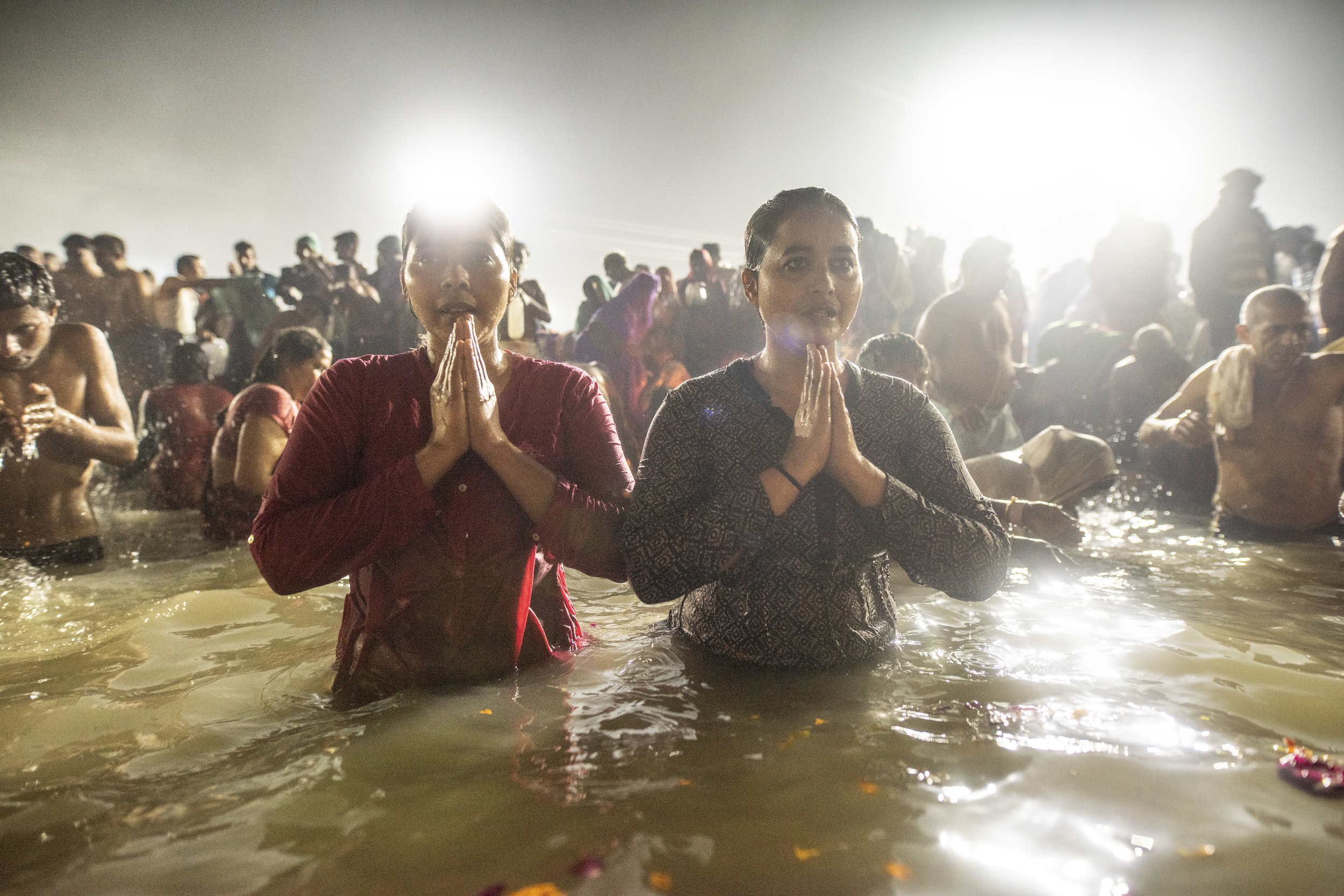 Two young women pray in the Ganges