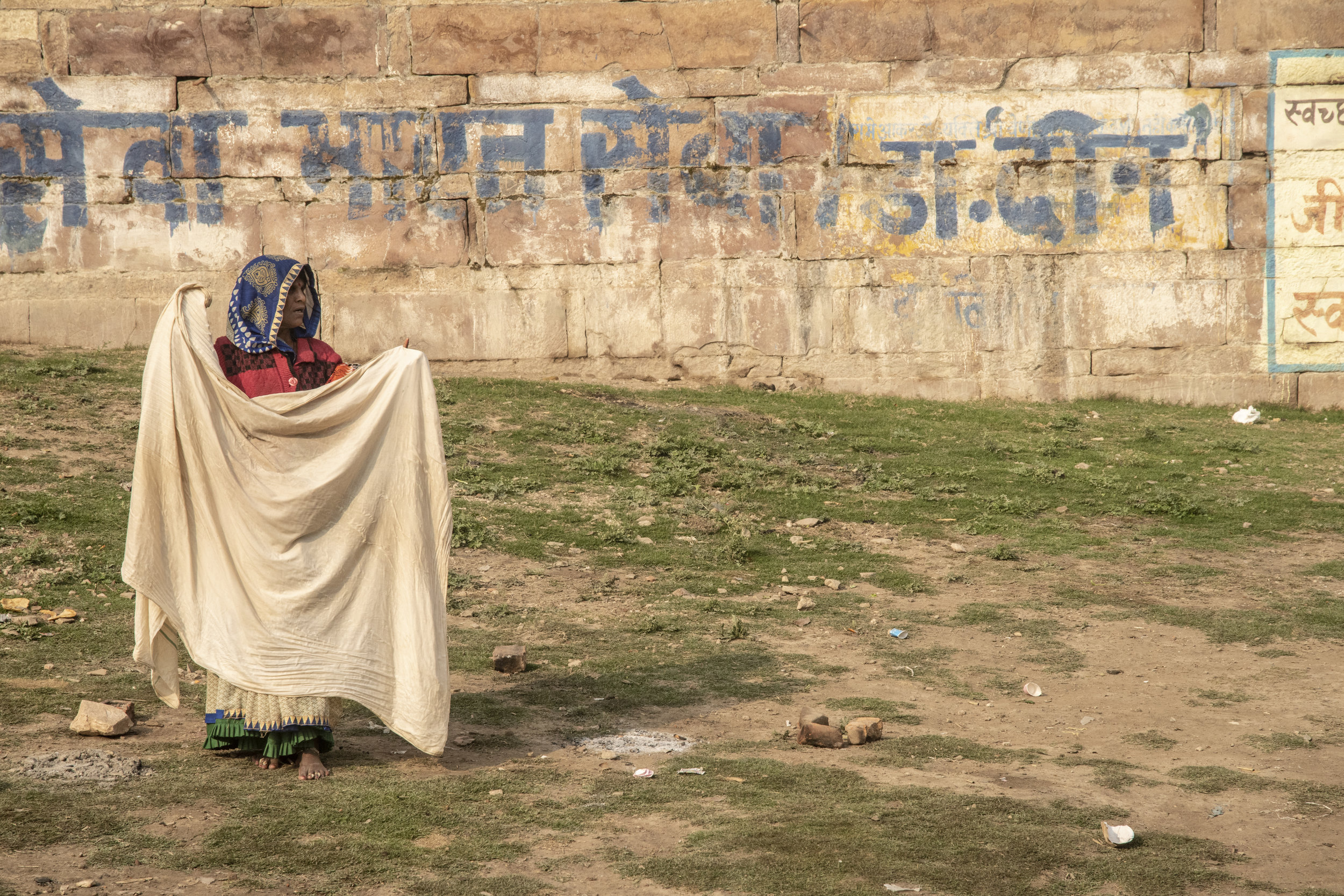 Woman stands afield, drying clothes in the sun