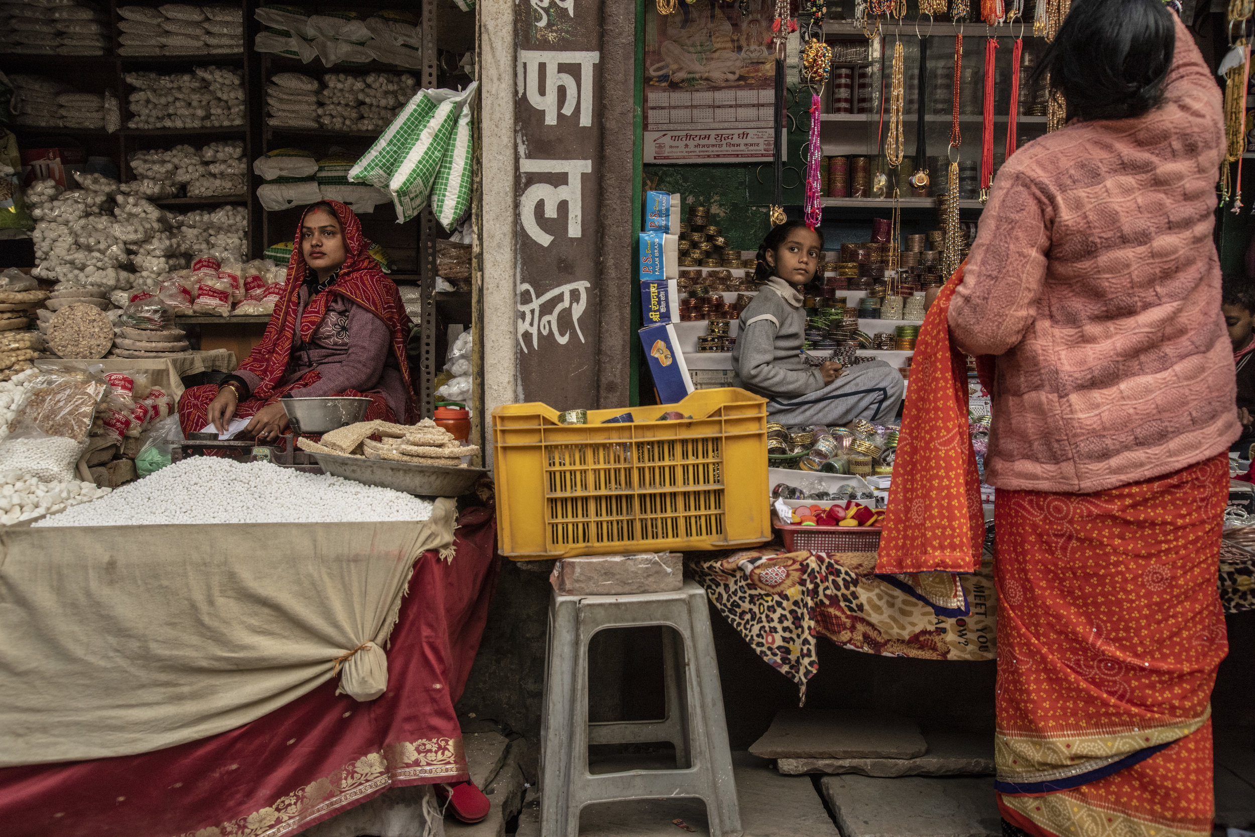 A woman and a young girl in a market in Allahabad, though divided, share the same expression