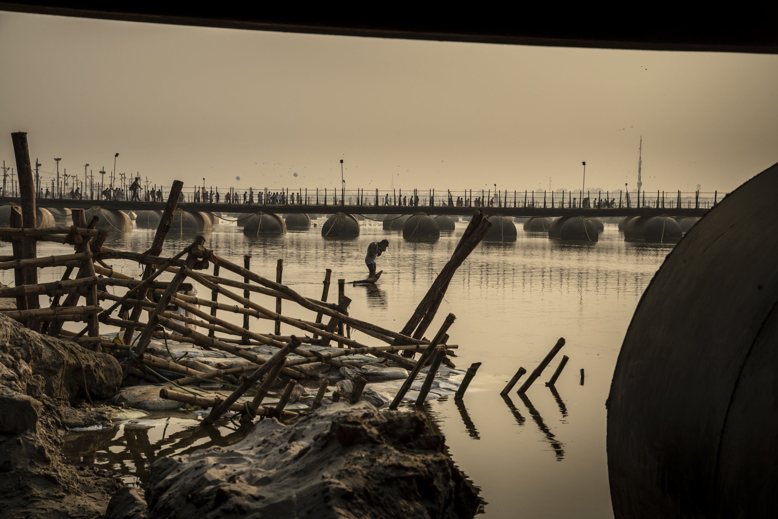 Man bathes in the Ganges betweenba series of temporary bridges