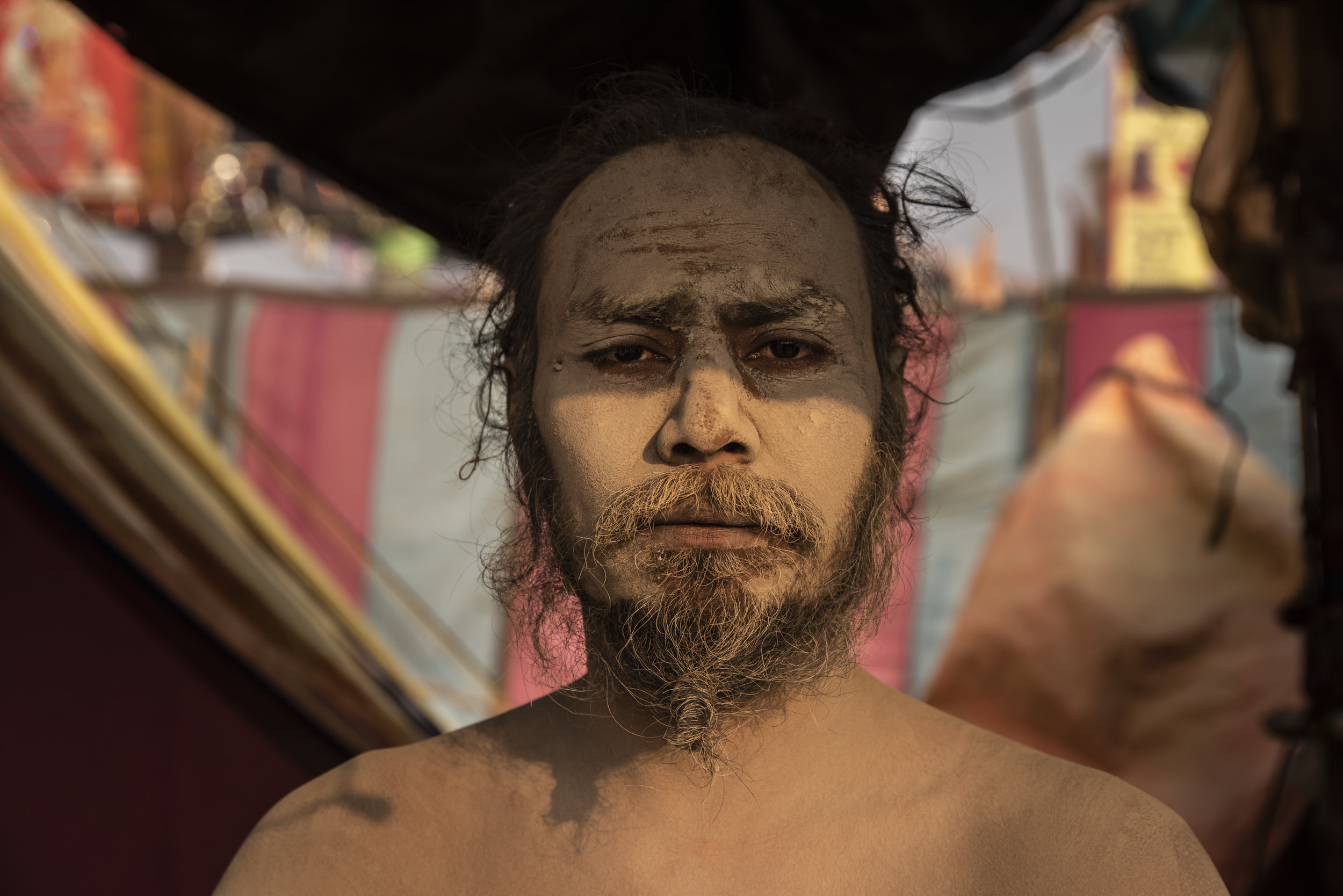 A Naga Sadhu meditates in his tent, offering blessings to those who pass.