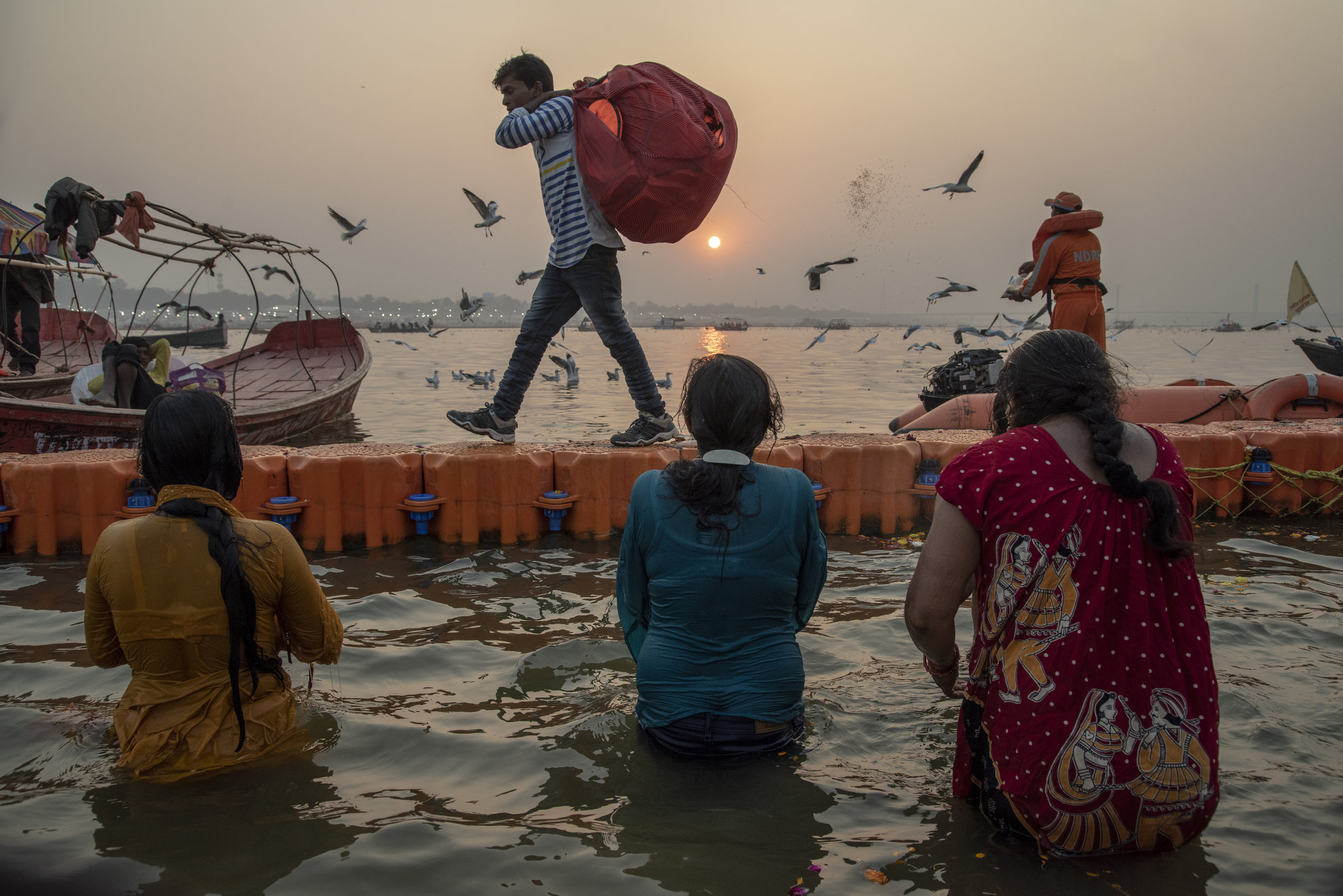 Three women bathe in the Ganges. A man carries life jackets along the barrier. Another tosses seed to the birds. Here at the rivers edge life gives and it receives. It preserves and purifies.