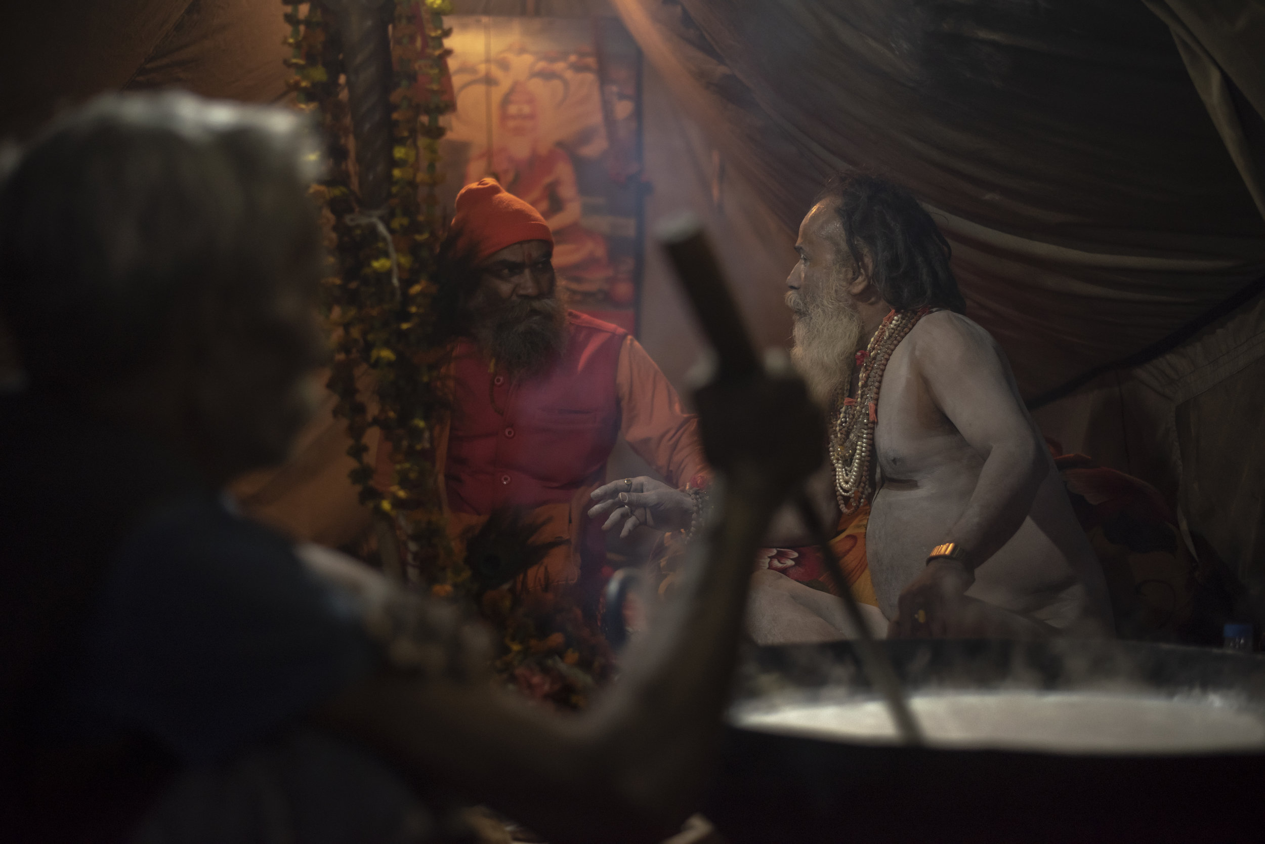 Two sadhu's (Hindu sages/priests) converse while a man stirs a giant kettle of milk representing the Samudra Manthan, an auspicious ocean of milk from Vedic mythology.