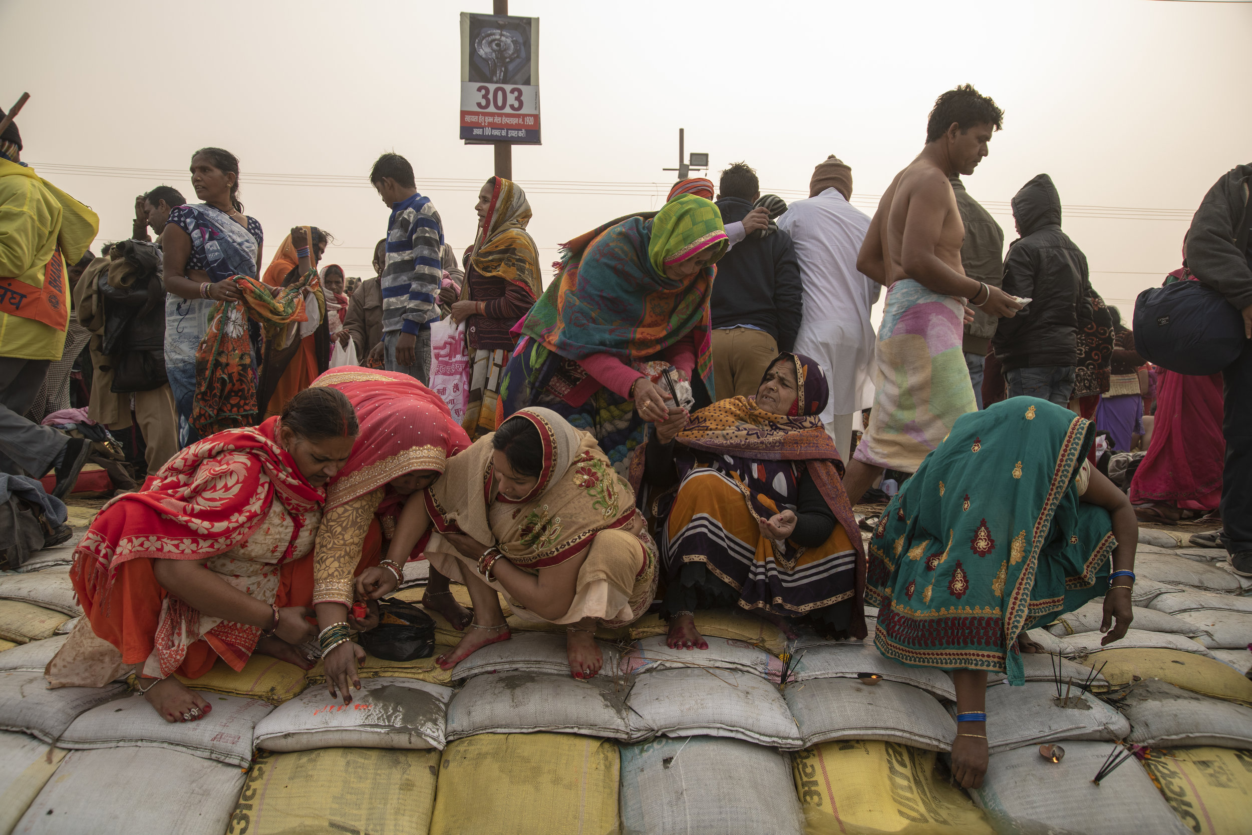 Women gather along the shore of the Ganges to give puja offerings