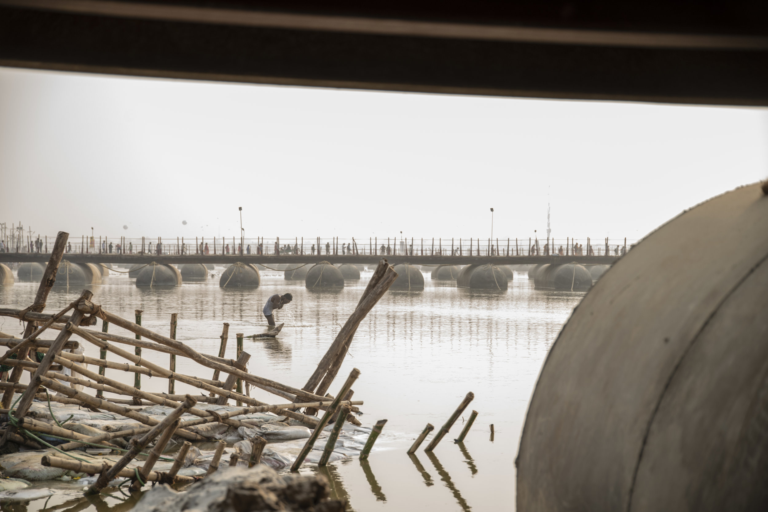 Man bathes in the Ganges between two of the temporary bridges built to allow passage to and from the mela.