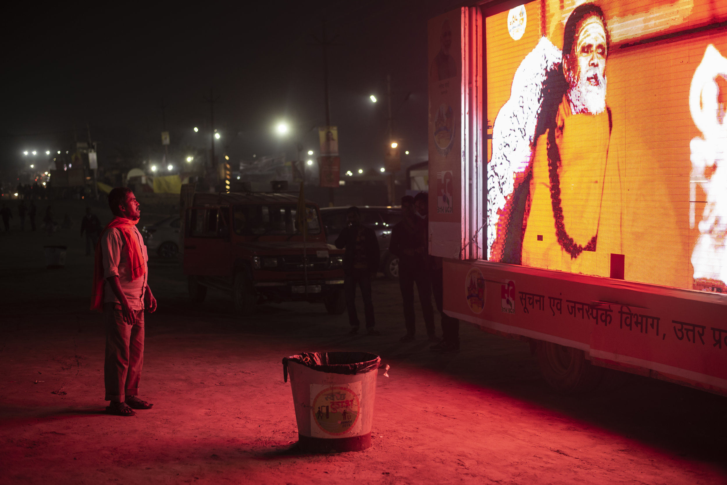 A man stands, captured in crimson light, downloading the teachings from the glowing roadside sadhu. Here at Kumbh consciousness moves. It is pulled and pushed. For some it shrinks and others it expands.
