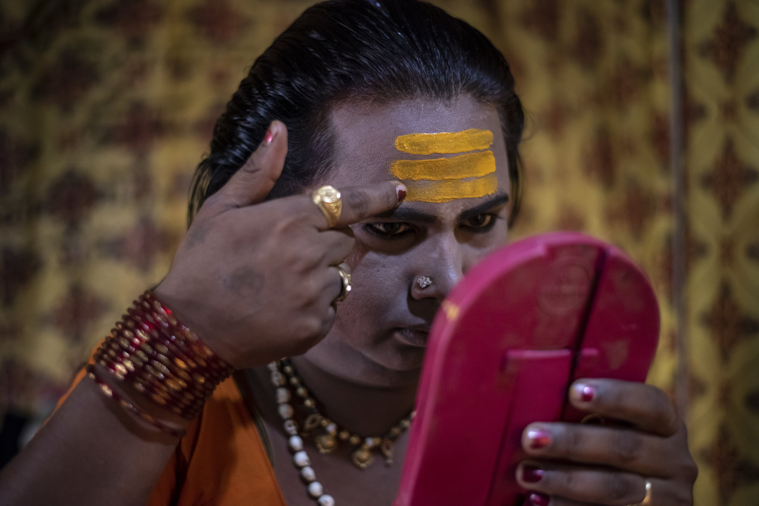 A Kinnar Akada (transgender) applies makeup