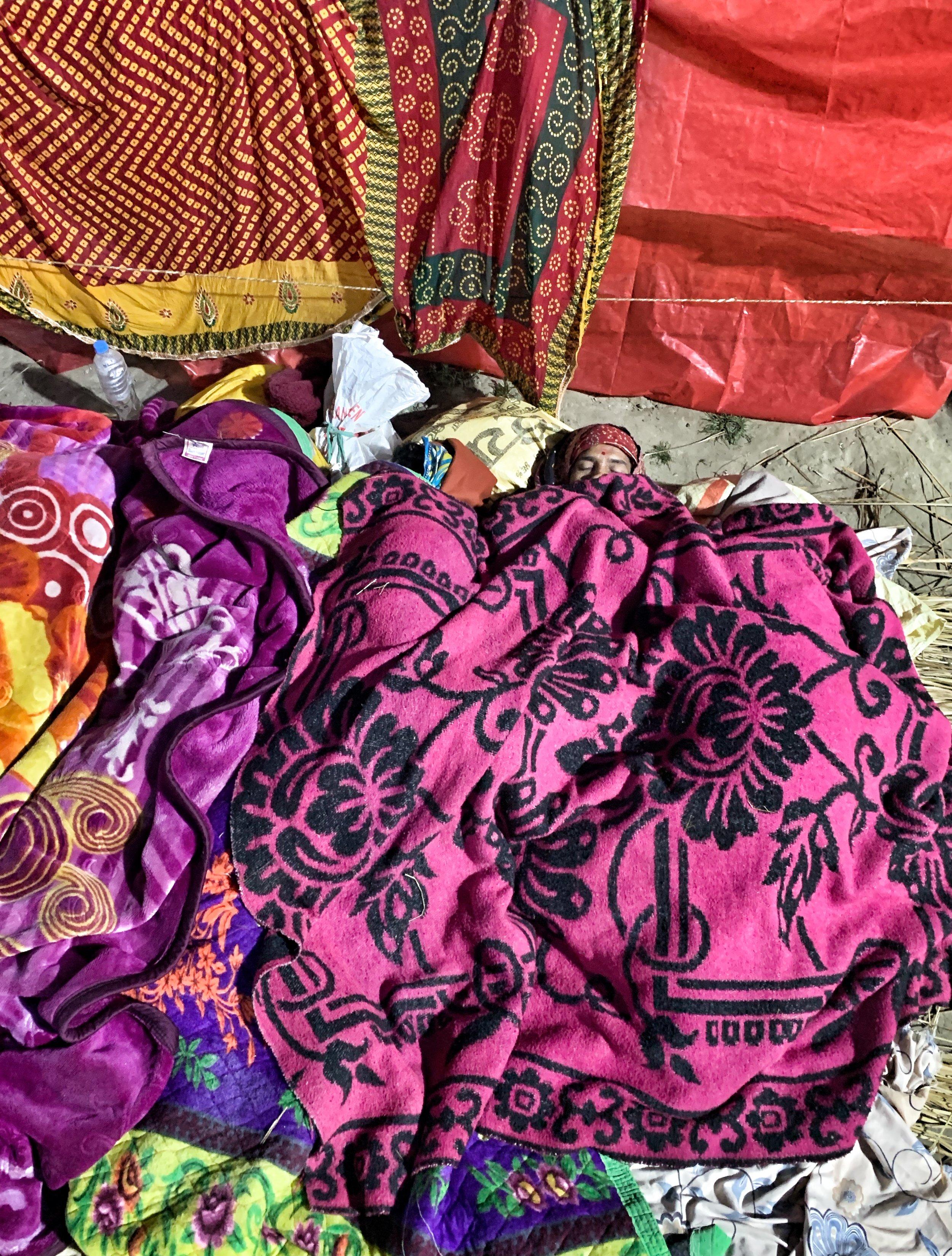 Man sleeps in an ocean of colored fabrics.