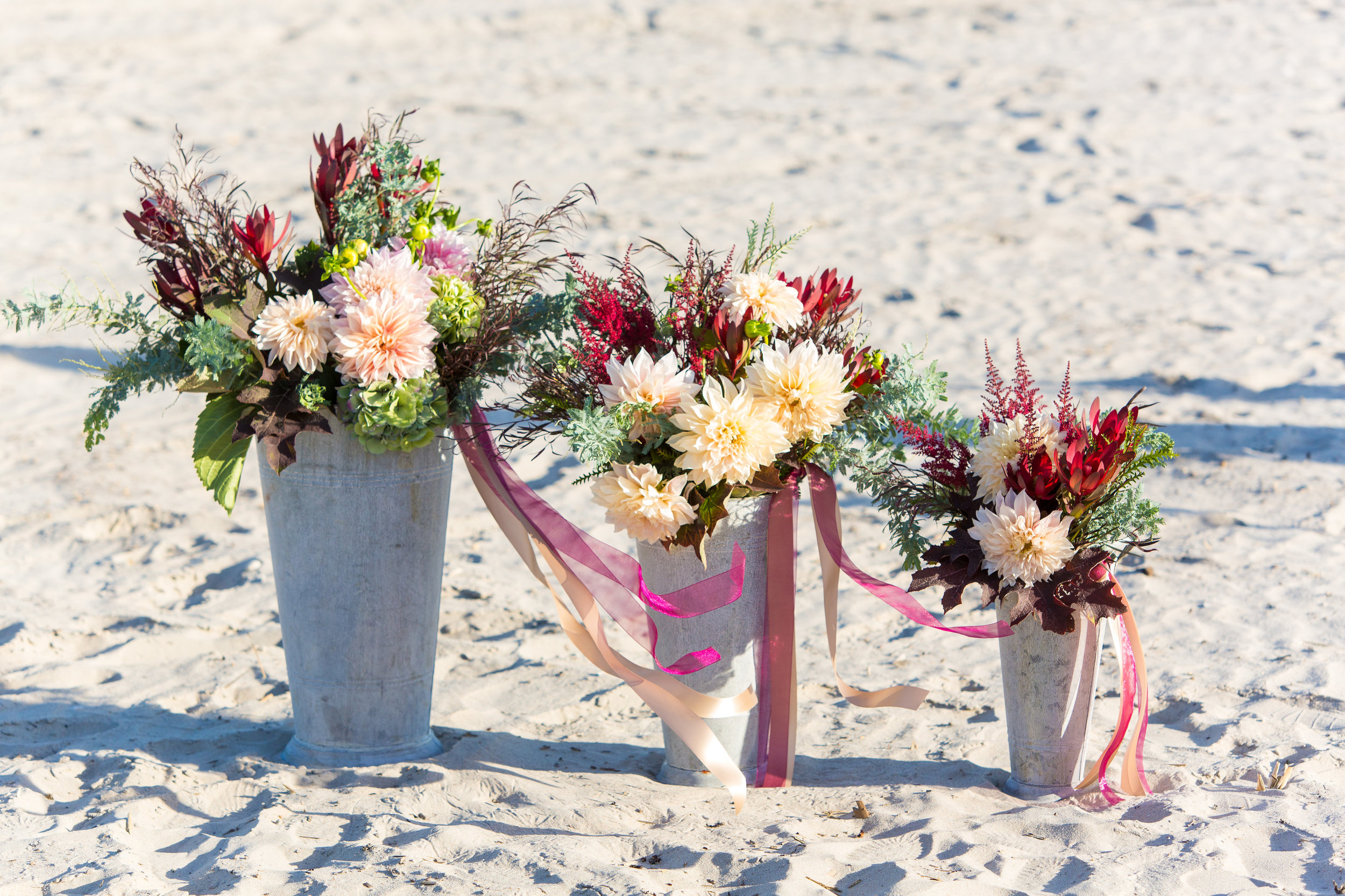 These buckets have never let us down for beach weddings. The buckets themselves are casual enough on their own that we can go all out in packing them full of lush arrangements of flowers. For Jenna and Jon's wedding, we used huge dahlias, astilbe, hydrangea, greenery and leaves for bright colorful designs, and the ribbon tails gave such pretty movement in the breeze.