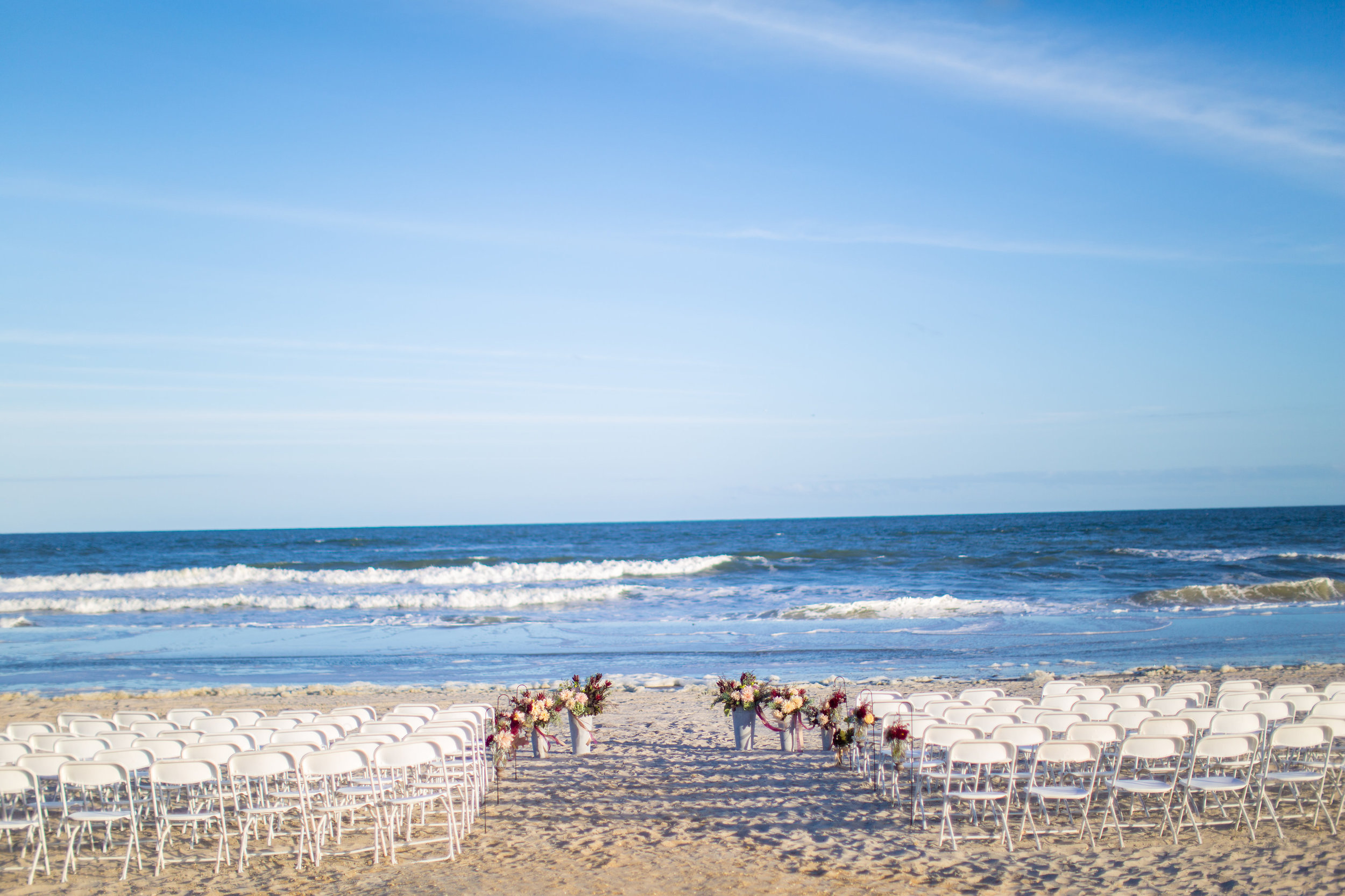 We loved the simplicity of Jenna and Jon's ceremony space. The white folding chairs leave little to distract from the crashing waves of the ocean and blue skies. The pop of color in the aisle arrangements and galvanized buckets at the altar brought all the focus to the couple as they said their vows.