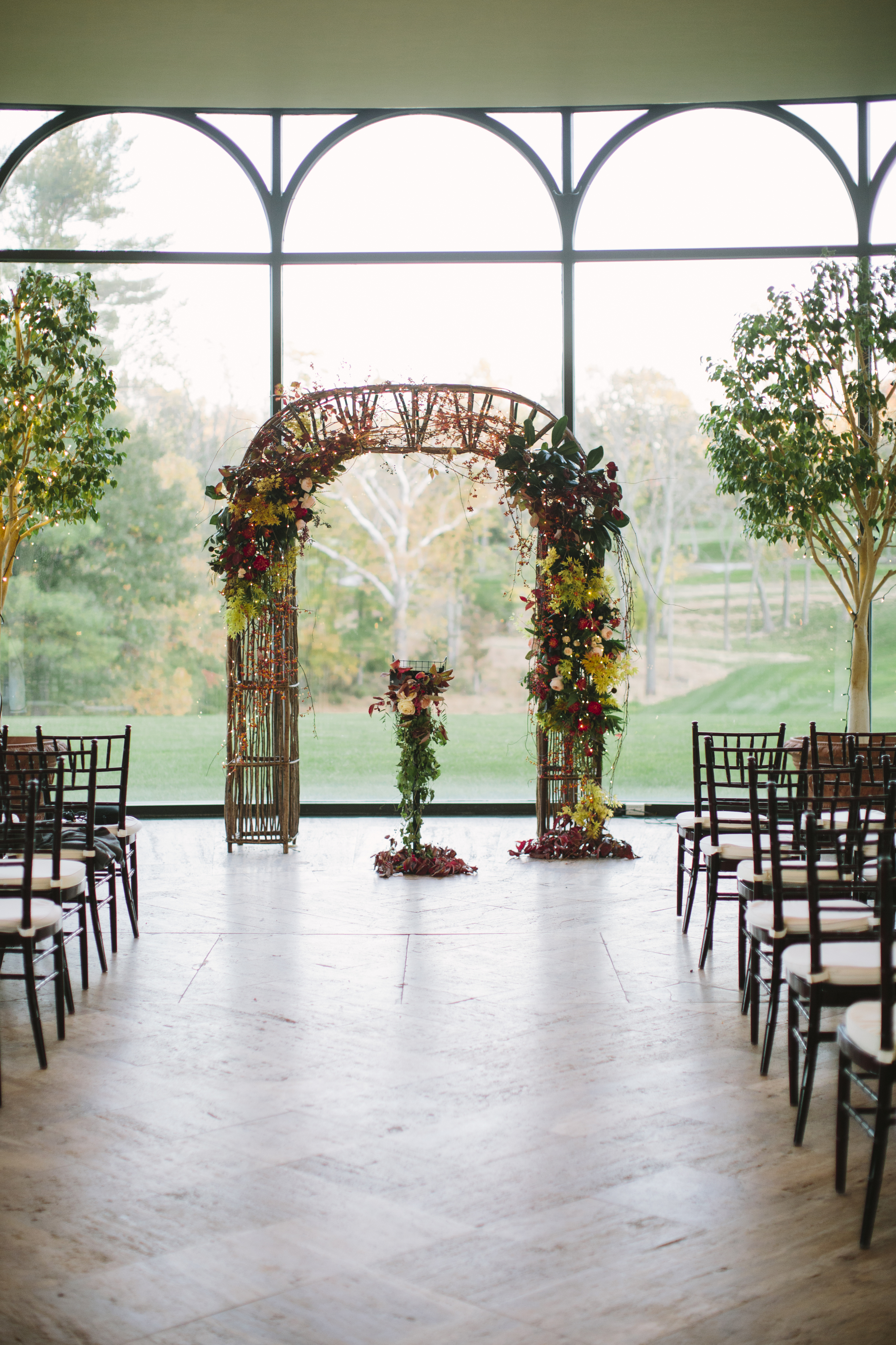 Our  willow arch  was used for the couple's ceremony, and we were giddy to be able to design with Emily's vision. Our bride wanted wild and gardeny florals, and strands of fairy lights really brought it to life. We wanted this arch to be an extension of nature's fall performance, and are so happy with how it turned out. At the last minute, a podium was added, and it served as a great excuse to create a central point to the design with vines winding their way up and down the stand.