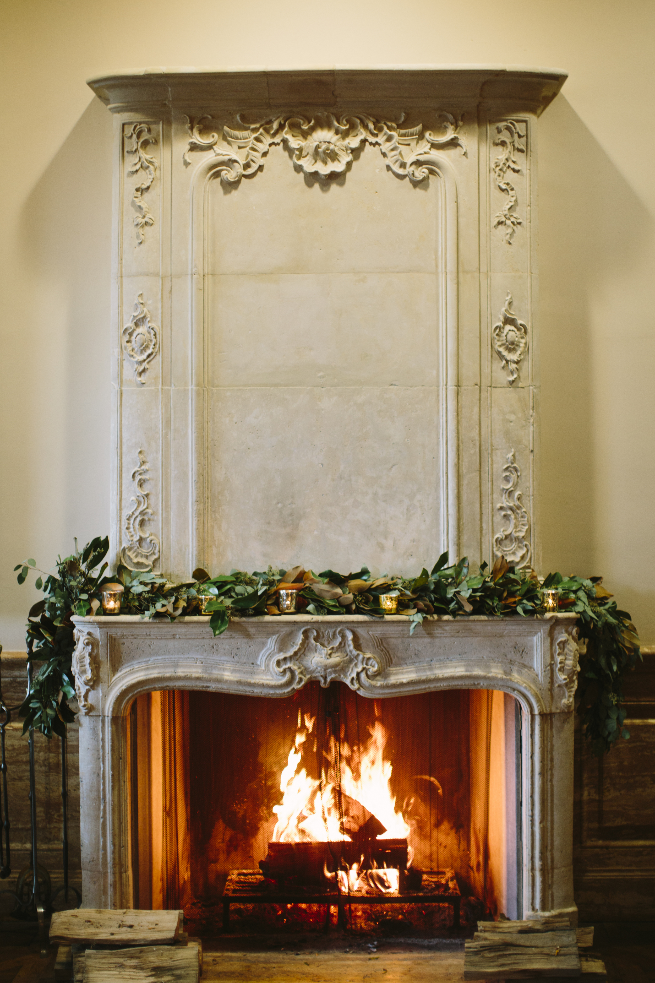 How cozy does this roaring fire look?! This ornate mantle was softened a bit with gold mercury votives, and a garland of magnolia and eucalyptus leaves.