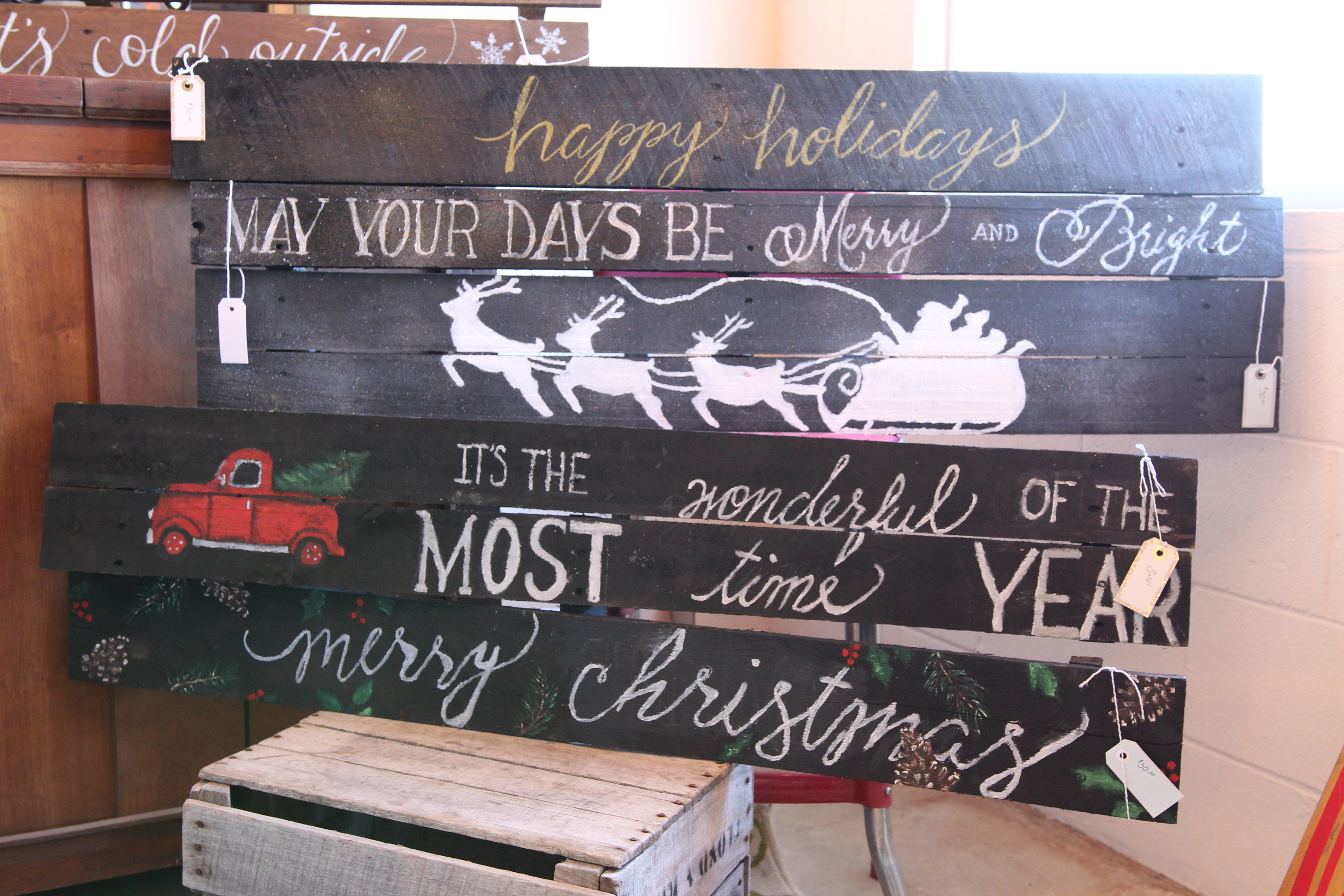 Our own in-house artist, Cristina, came up with some original wooden signs for your holiday mantle display.