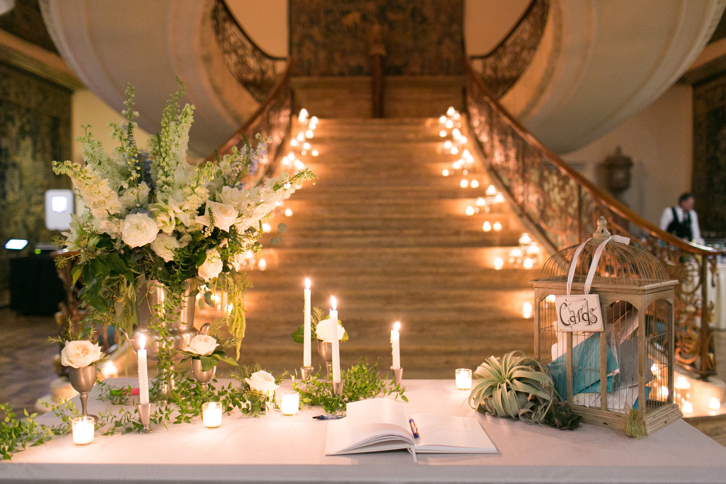 There's that staircase we were talking about!  Lined with dozens of floating candles, it serves as another perfect backdrop for this wedding's decor.  Here we're featuring the guest book table, with scattered votives and tapered candles lighting up the card box and guest book.  Scattered smilax, pewter pieces with rose heads, and a pewter champagne bucket holding an arrangement of white orchids, roses, and greenery complete this serene setting.
