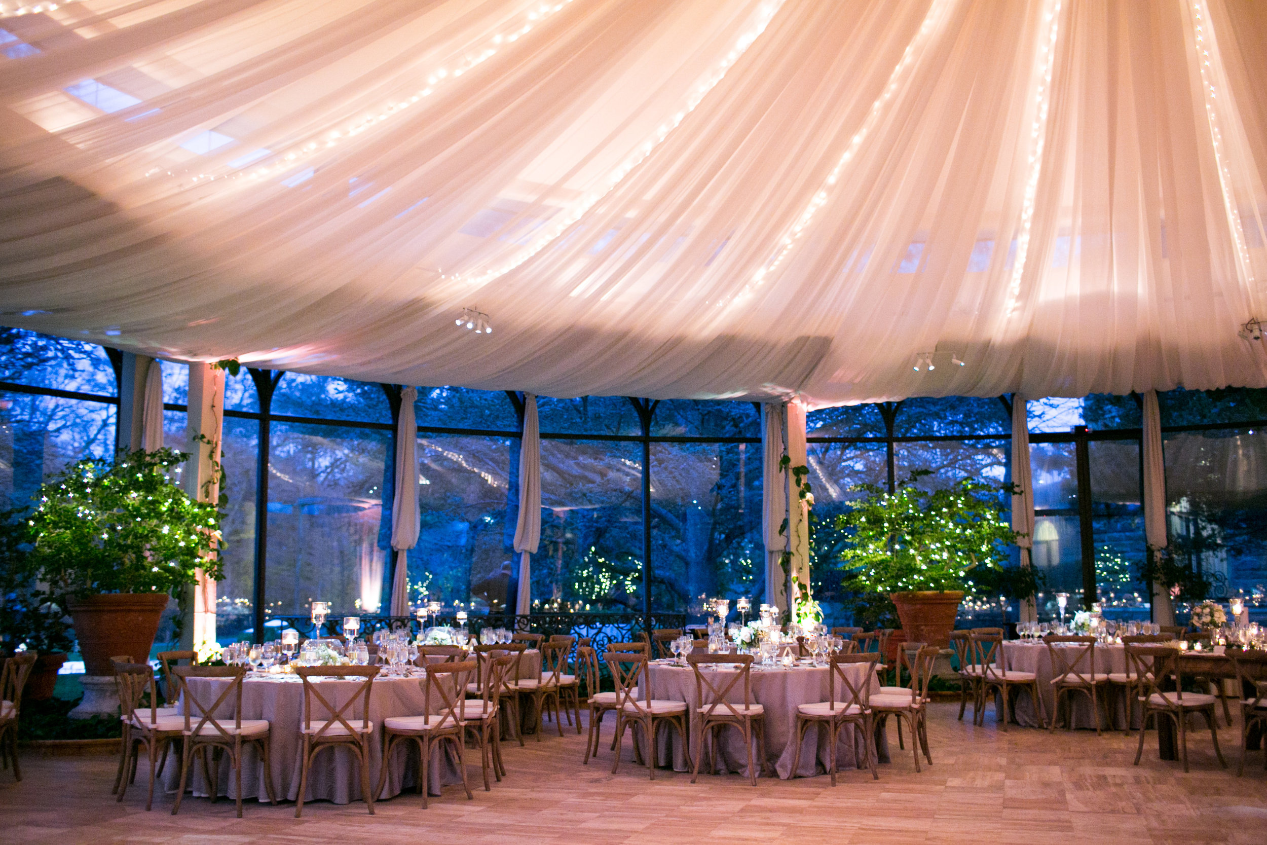 This reception room is to die for!  Sarah and Steven added draping to the ceiling for an extra dramatic flair, with string lights bringing even more ambiance to a room filled with candleight.  Jasna already provided the giant planters with trees dazzled with more string lights to brighten up the room and break up the window space.