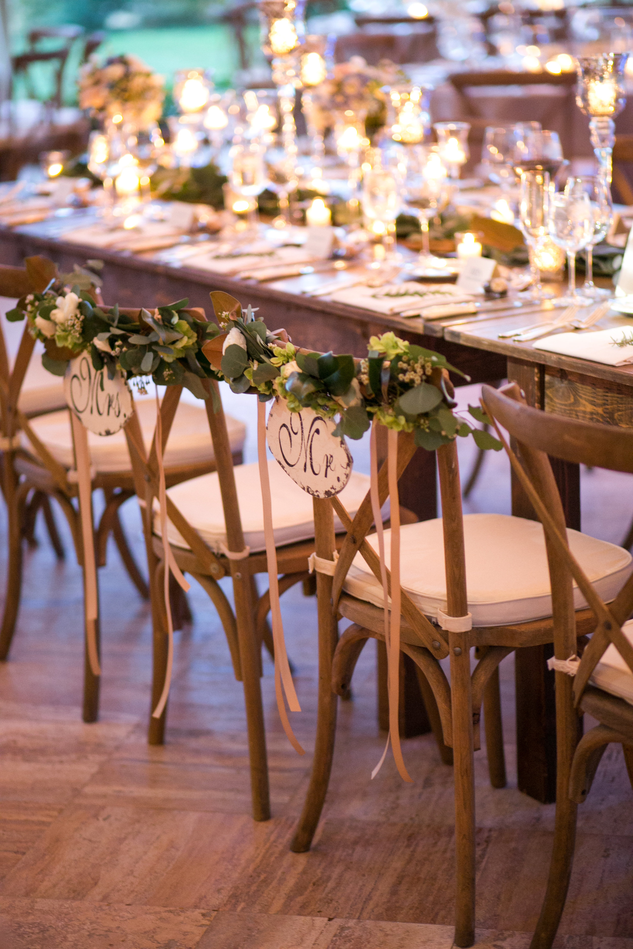 "Rented wooden farmhouse tables from  Rustic Drift  warmed the room against the marble floors.  We also loved the chair detail Sarah and Steven requested, with greenery embellishing their ""Mr"" and ""Mrs"" signs."