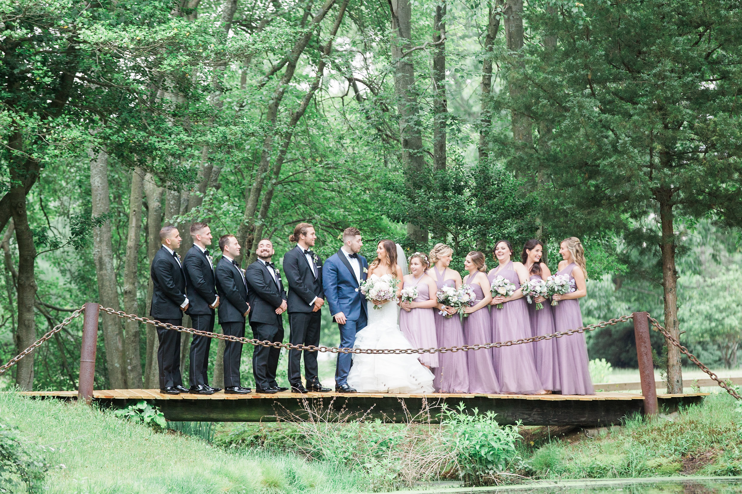 bridal party on bridge in woods