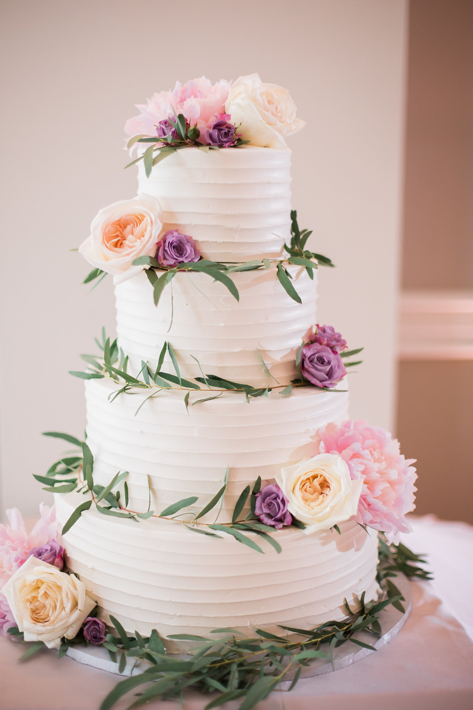 tiered cake with blush and purple flowers