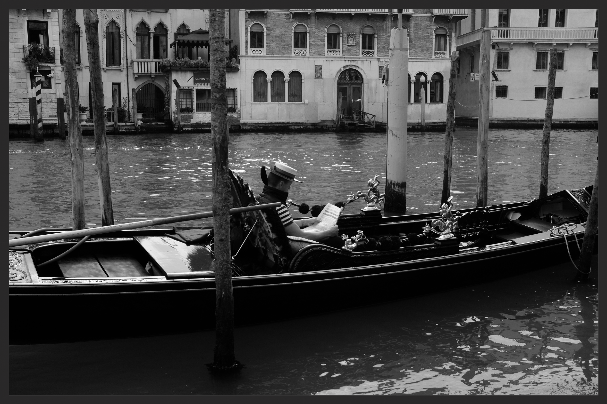 A gondolier reads the newspaper on the Grand Canal.