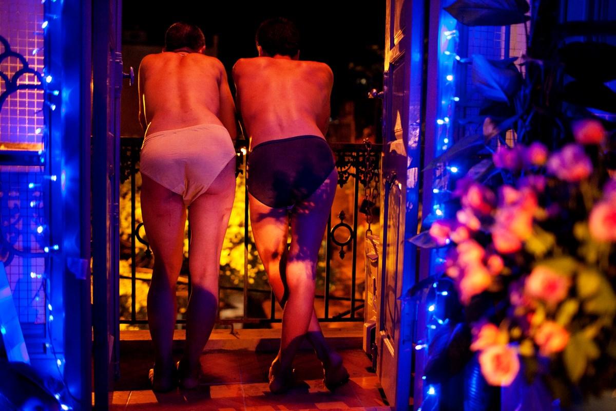 2011年7月22日、ハノイの自宅のバルコニーでたばこを吸いながら話すLe Nam HaiとHoang Minh Tien。出会ってから13年。ともに10年以上HIVと生きている。