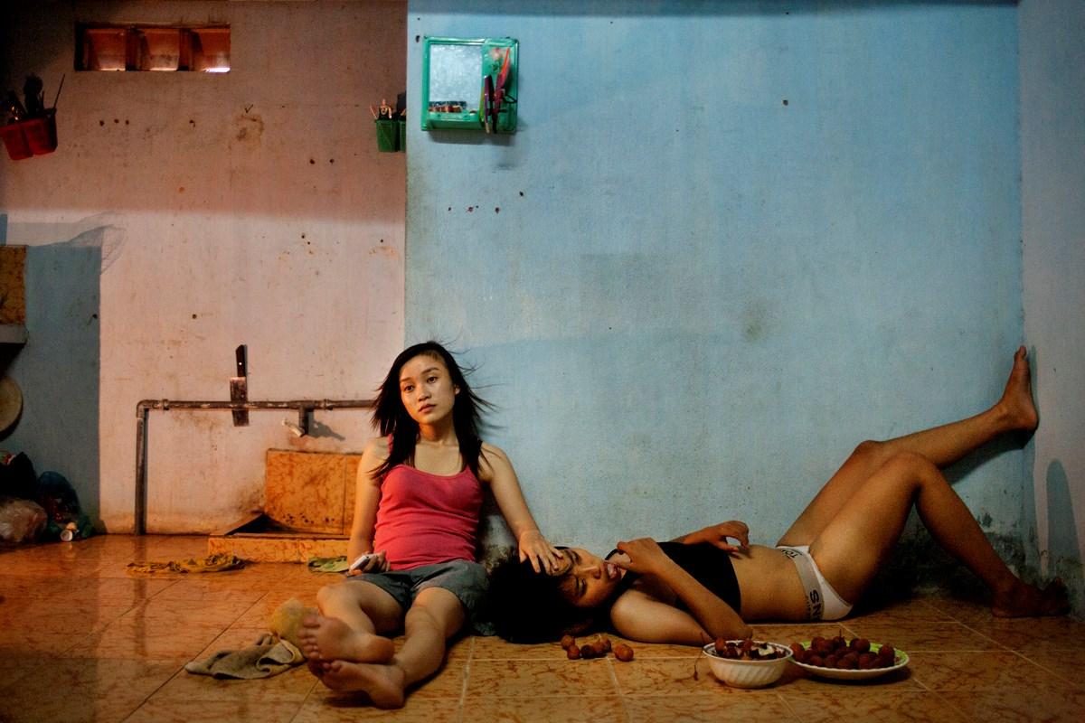 2012年6月22日ホーチミン、1日の終わりにテレビを観てくつろぐ学生Phan Thi Thuy VyとDang Thi Bich Ba。付き合って1年になる。