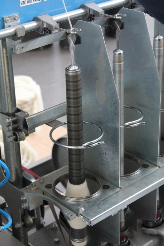 The spinning frame is used to draft and twist the singles then ply the singles together to create the yarn