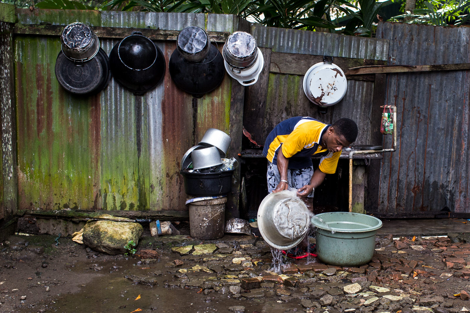 Washing the dishes in the morning, Yosua is in charge of most of the household chores.