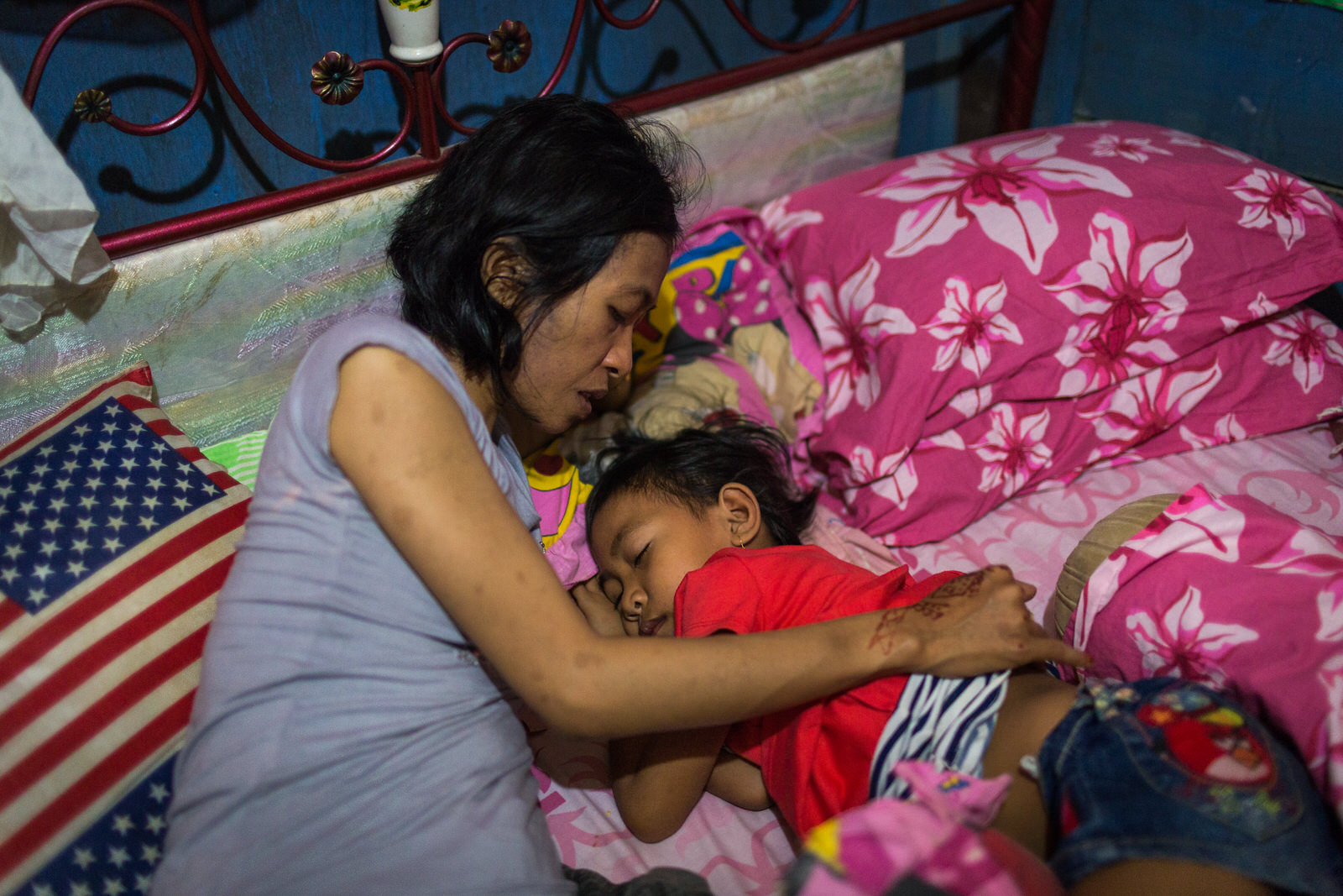 Singing a lullaby, Ibu Ratna tucks Amel to sleep.