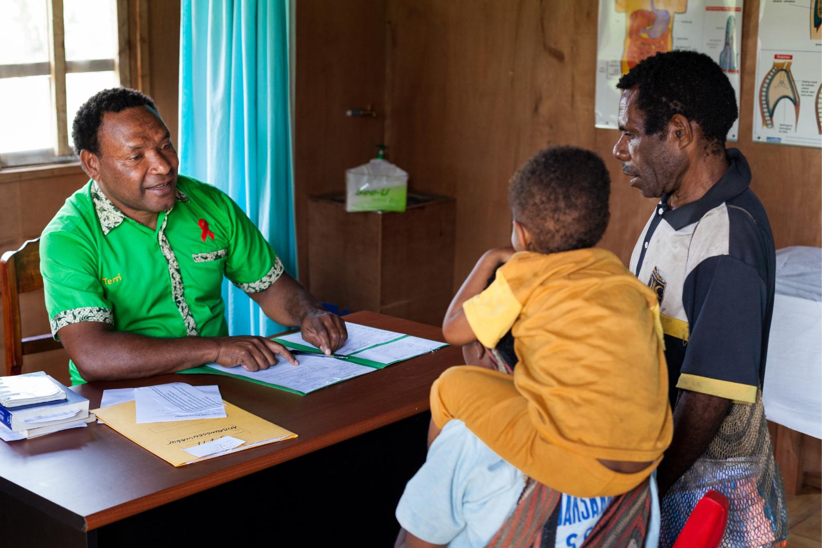A nurse at Klinik Kalvari in Wamena counsels a family during a checkup.