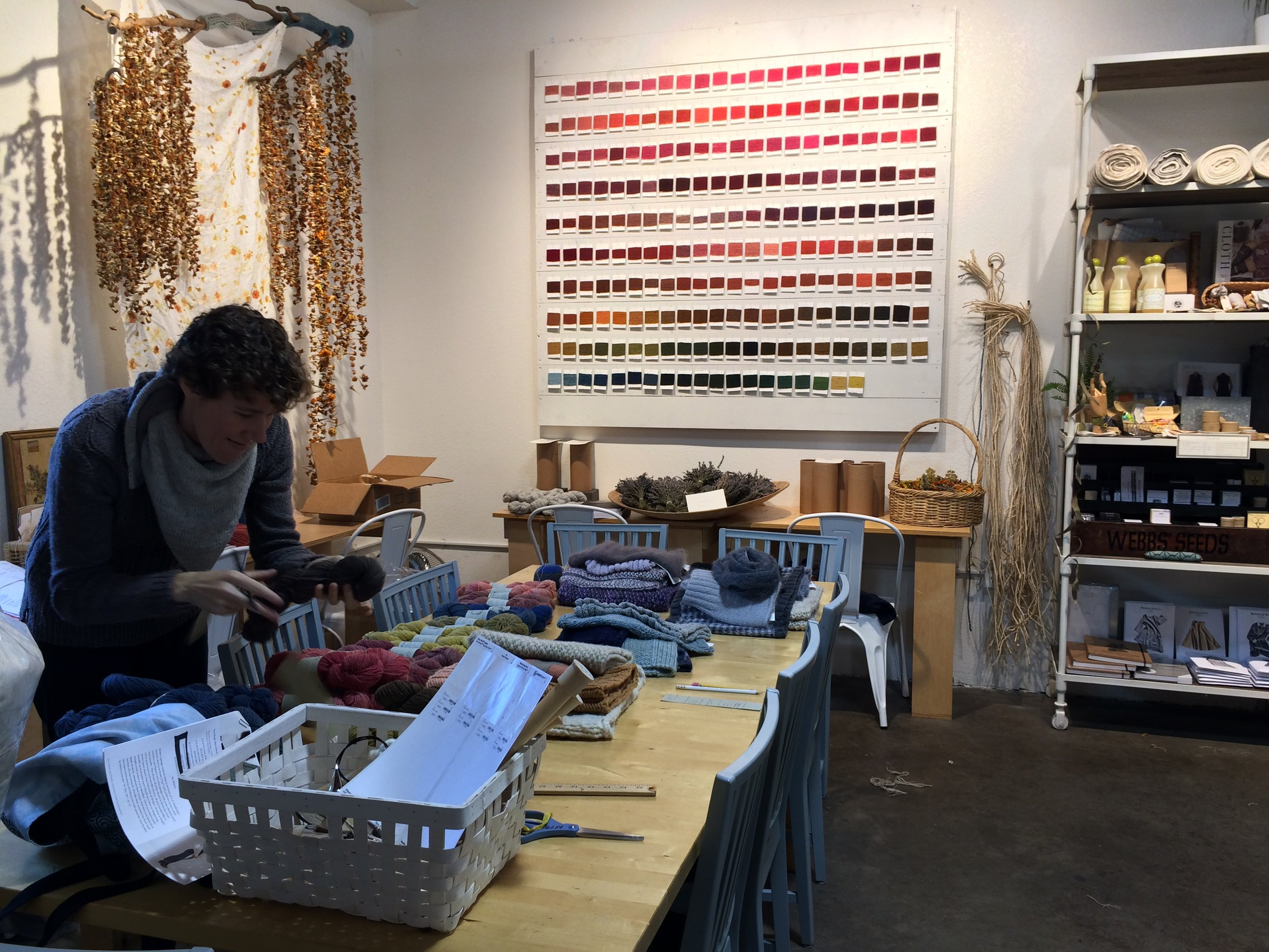 A long table hosts classes in natural dyeing, knitting, sewing, spinning, and weaving, surrounded by natural dye shade cards, lavender, and whole dyestuffs