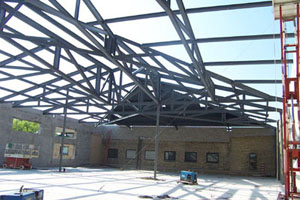 Fitness Center:  A complicated geometry of hips and valleys made this a challenging project for our drafting department. Creating a 3D model of the entire framing ensured that every piece of steel fit to amazing precision.  The site conditions created another challenge for us. A small jobsite with limited storage space, an adjacent building open for public use and large components for the roof trusses required deliveries be carefully coordinated and well planned. The configuration of the roof framing required two cranes. While one crane held the main truss in position the second crane placed the adjoining trusses stabilizing the entire system.  The job was completed on time with a high level of safety and no incidents or accidents.