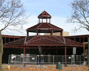 Newport West Gazebo:  The incredible feature of this non-conventional gazebo is that the entire structure is clear span, self supporting and the inside is open all the way to the peak. Much time was invested in the planning and coordination of this non-conventional gazebo.  The incredible feature of the gazebo is that the entire structure is clear span, self supporting and the inside is open all the way to the peak. This was achieved by leaning shop fabricated moment frames at the corners into a compression ring. The Asymmetric pattern of the structure complicated the process. A temporary tower at the center of the structure was installed and was removed after the entire field welded moment connections were complete. To complicate things further, being built on a city lot, the delivery of the components had to be carefully coordinated so not to choke the other activity on the site. The temporary tower was supported on anchor bolts with double nuts so the tower could be gradually lowered and any deflection of the structure could be monitored. There was only one eighth of an inch drop after the tower was removed. The time invested in the planning paid dividends as the structure was completed weeks ahead of schedule.