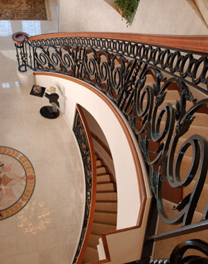Oconomowoc Residence:  Ornamental iron gives this room a more substantial feeling and adds significant value to the home.  The owner wanted to create a spectacular impression for guests entering his home. This was our only instruction on designing the curved stair railing. By using ornamental iron as opposed to the traditional wooden balustrades it gives the room a more substantial feeling and adds significant value to the home. Most people are surprised at the affordability of custom built wrought iron and the uniqueness it provides.