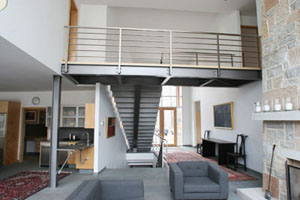 Mequon Residence:  The design of this contemporary home incorporated a clean irregular shaped stair that seems to have its treads floating in space. This was accomplished by using a single steel tube for the support stringer and steel bent plates that formed the risers and blue stone tread supports. Every angle viewed of the stair provides a unique independent perspective. The structural steel bridge on the second floor and the stainless steel railings harmonize with their surroundings.