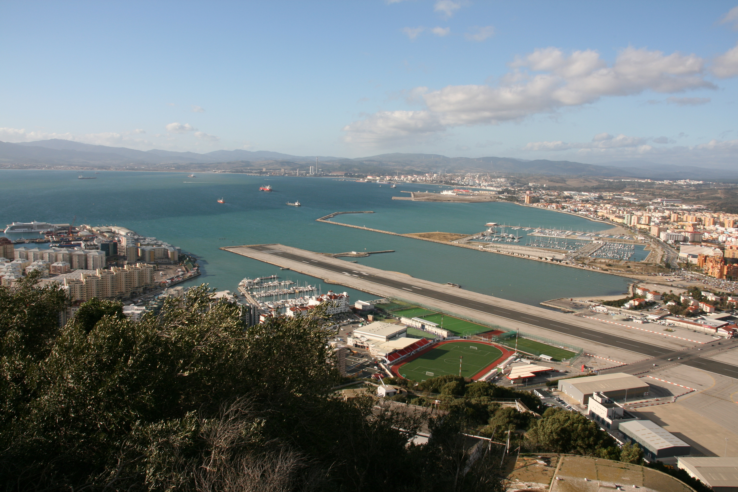 """The Great Siege Tunnels.  Gibraltar airport cuts though the entire territory. The main road connecting Gibraltar with Spain (to the right) has to be closed and the runway inspected when a jet is about to taxi and take off. The city of La Línea de la Concepción (short just """"La Línea"""") and its marina is to the right part of the photo. To the left: Gibraltar's Reclamation Areas and Ocean Village Marina featuring some luxury condos."""