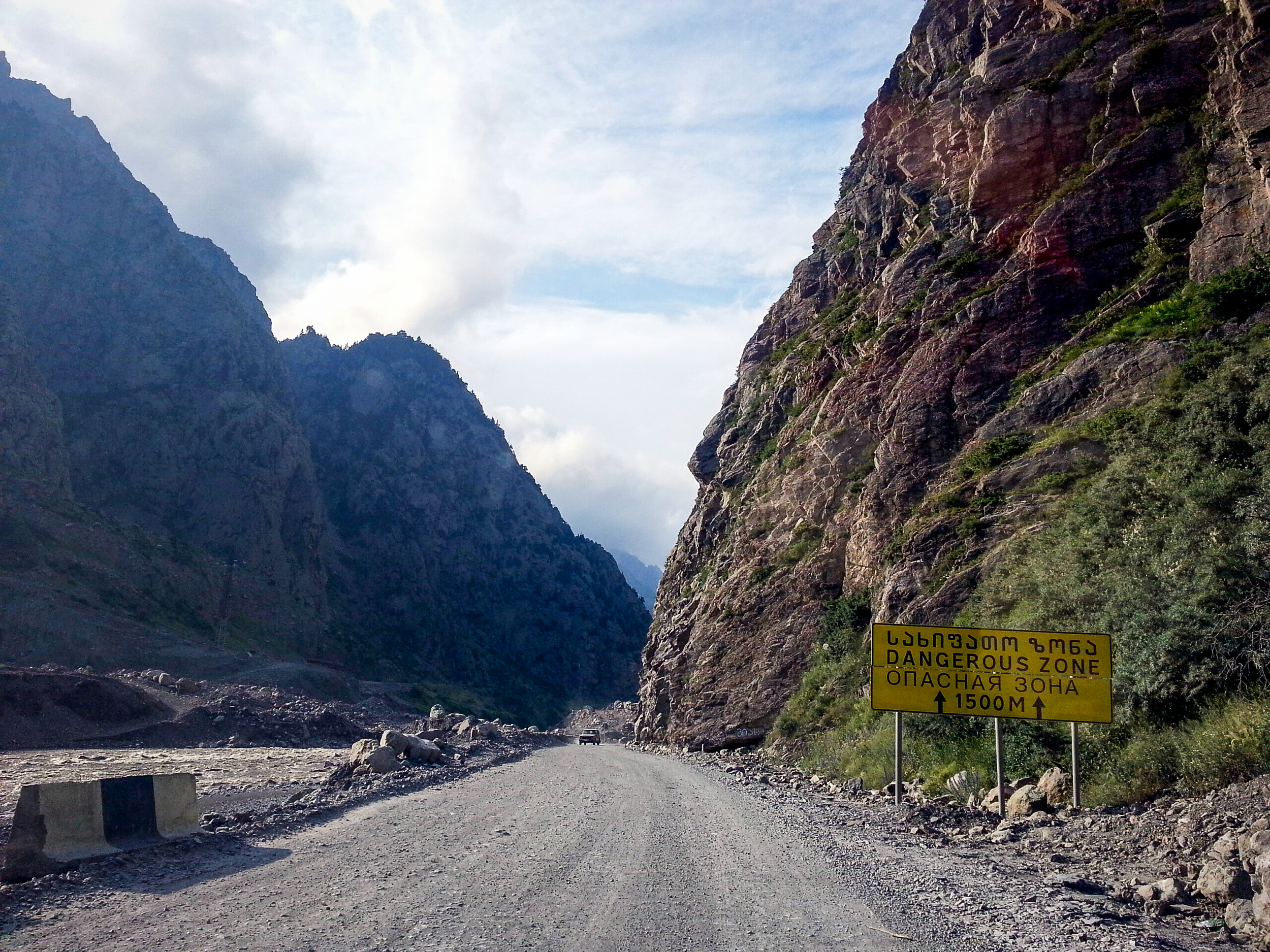 Caucasus . The Georgian Military Road shortly before the border. The rock slide has covered the old road and the tunnels completely under a 20-meter thick stone layer. Do you see the buried tunnel to the right after the sign?