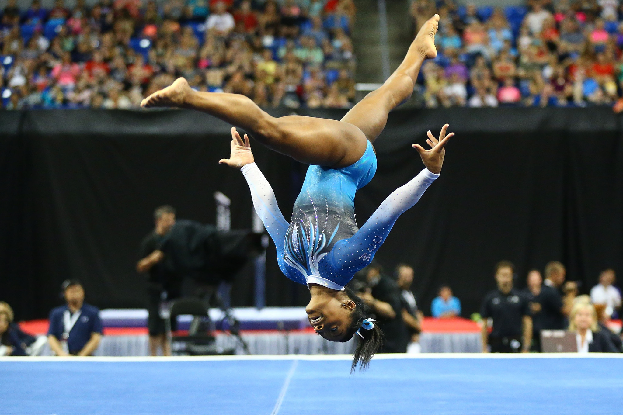 The floor exercise is about 40 feet long by 40 feet wide. The top layer is usually a carpet with a white marking around the perimeter. If the gymnast steps outside of this border, points are deducted from their scores.
