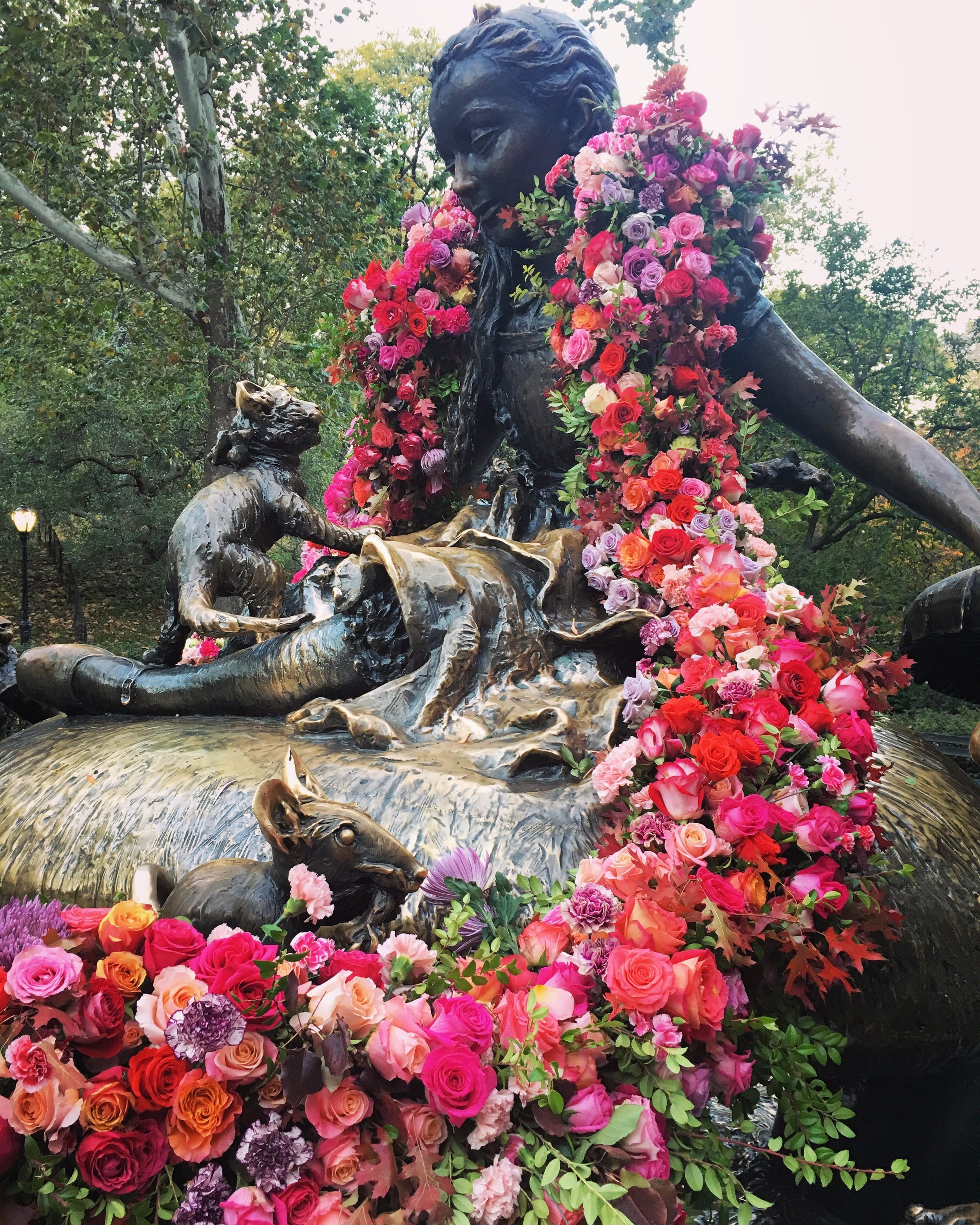 A garland of roses decks the beloved Alice in Wonderland statue in Central Park.