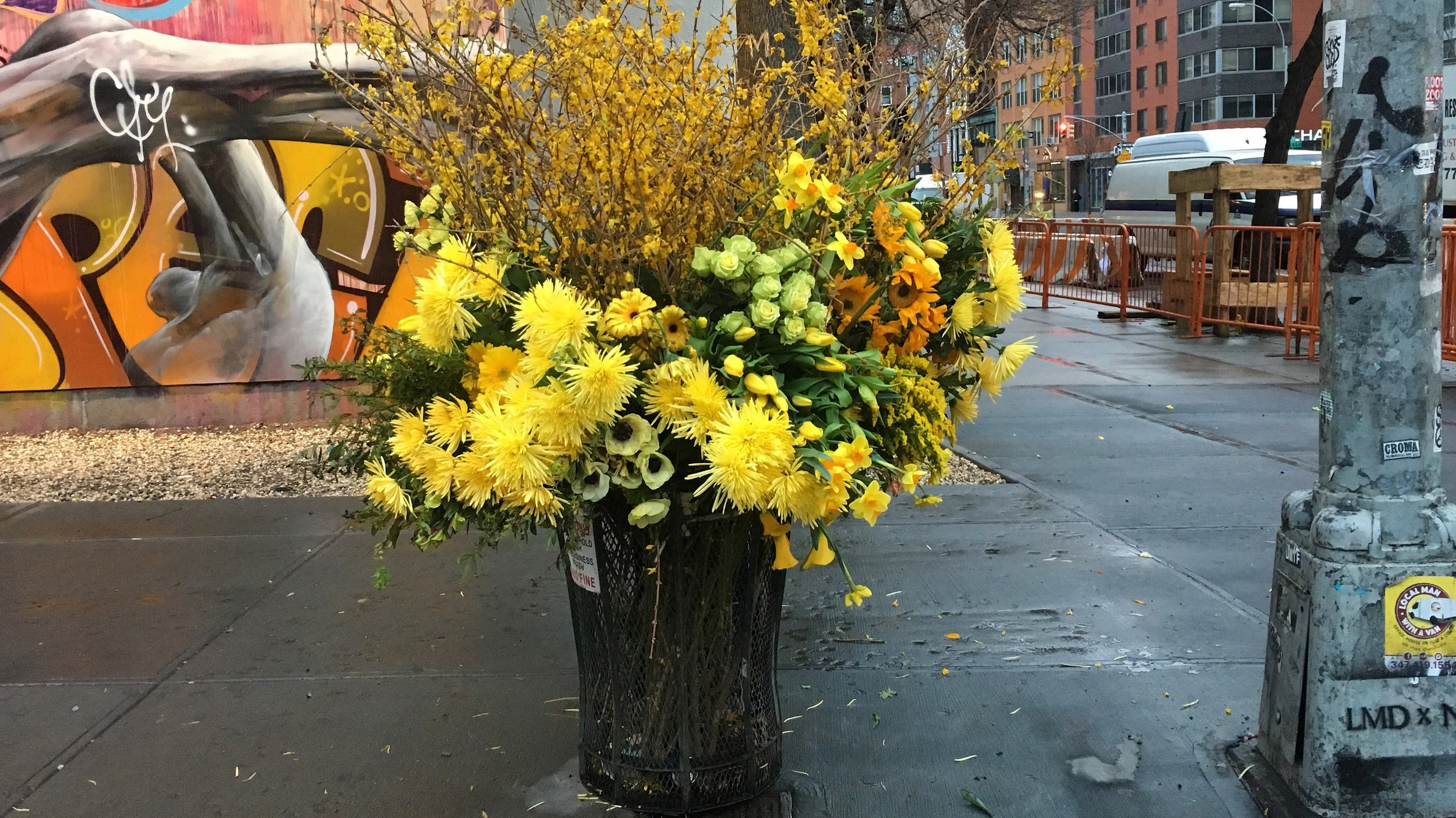 Trash bins overflow with sumptuous blooms.