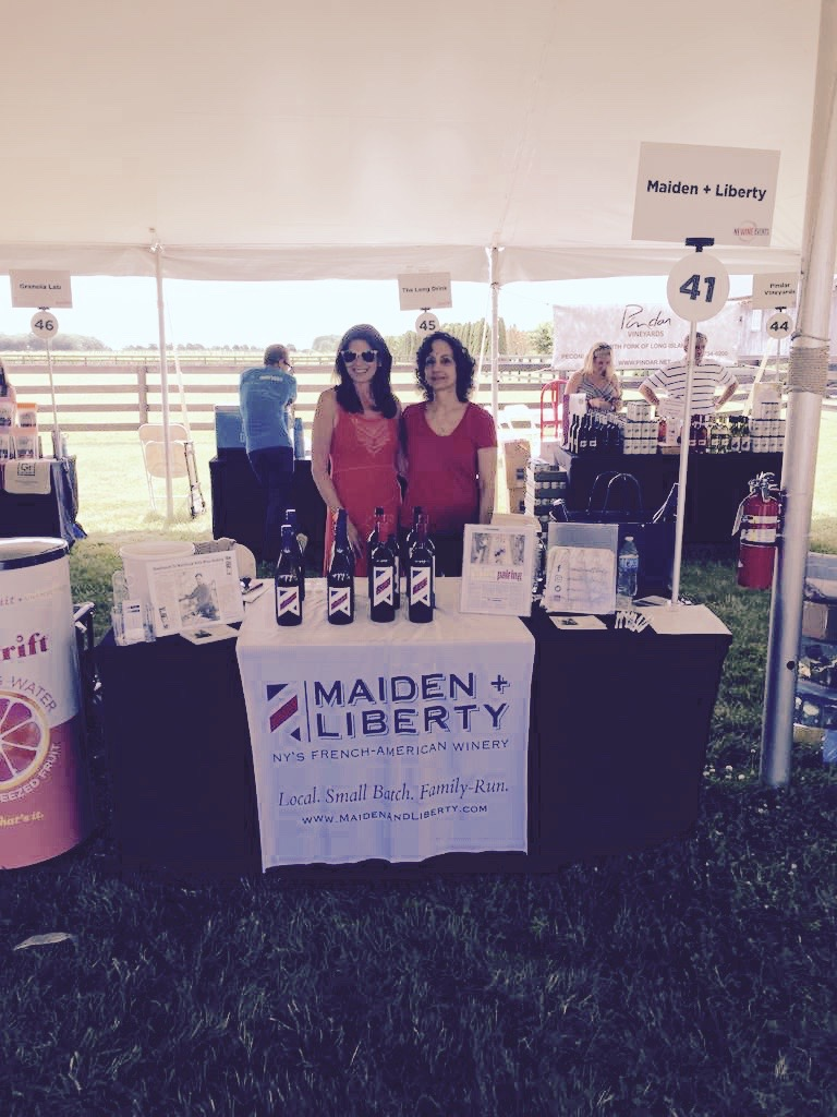 Our booth at North Fork Crush 2019 with two people serving our French-American wines to guests.