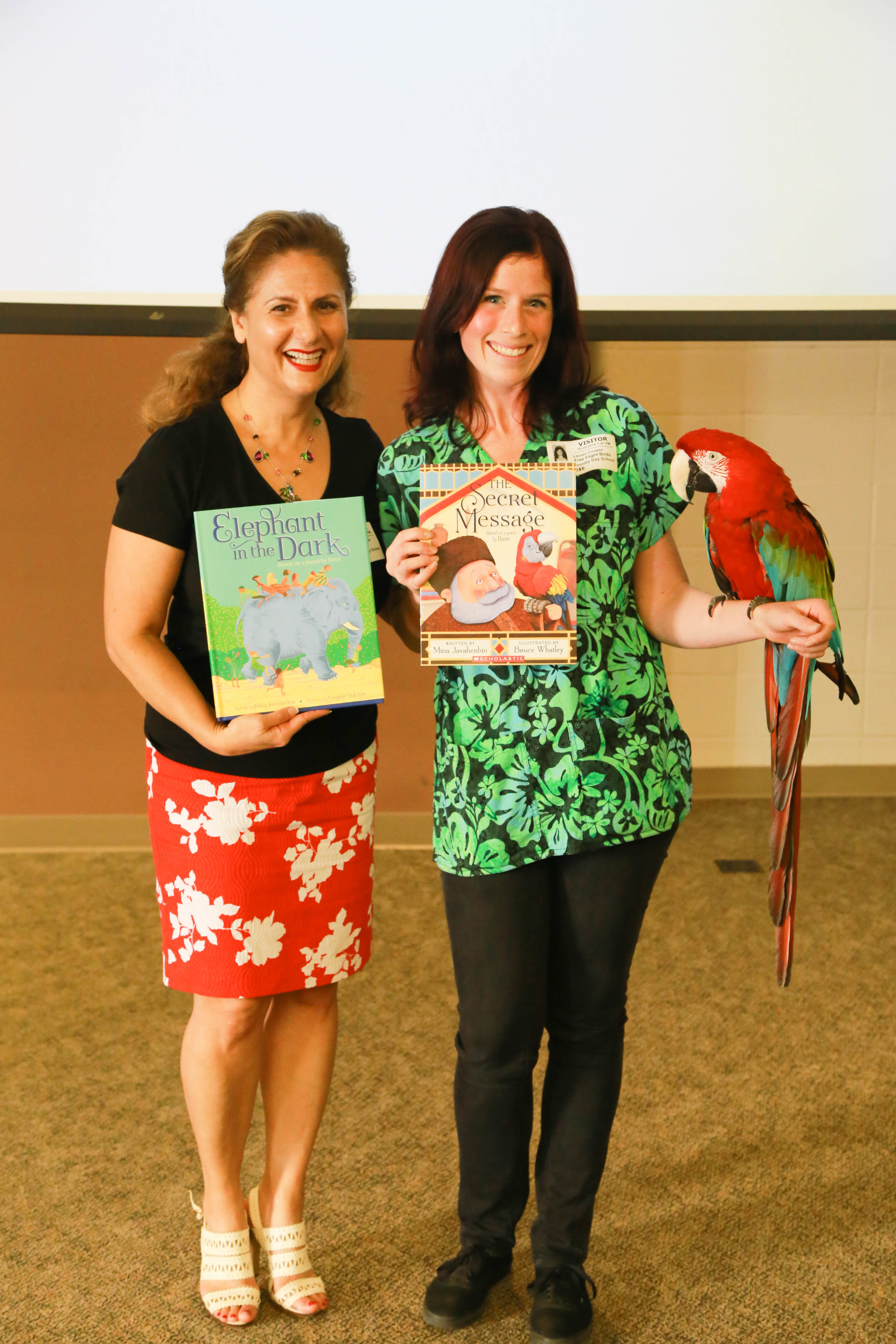"""""""Red,"""" the Greenwinged Macaw, meets Mina Javaherbin, author of """"The Secret Message"""" [Photo: Rachel Baxter, LJCDS]"""