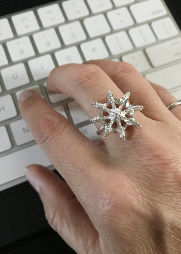 silver abstract starfish ring on middle finger. Oceanic themed jewelry worn to get excited about beach vacation while still at work and typing on computer keyboard.