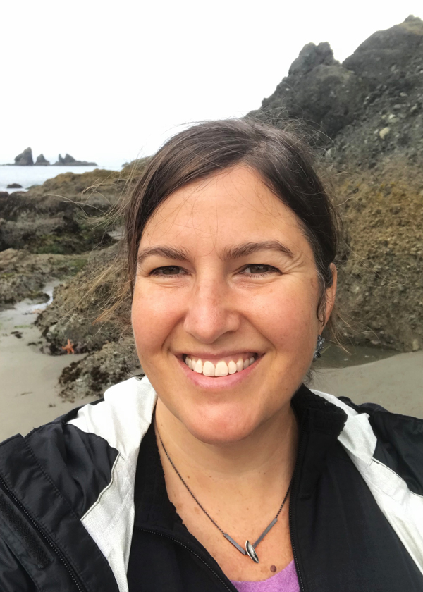 Catherine wearing black silver split bar leaf necklace in front of rock formations teaming with ocean wildlife at Shi Shi Beach on Washington coast Olympic Peninsula