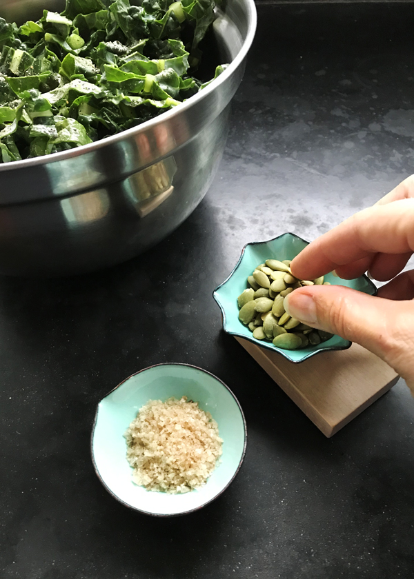 simple kale salad topped with smoked Maldon sea salt and pepitas. Little handmade enamelware salt cellar and nut bowl in turquoise and orange with individual wood base.